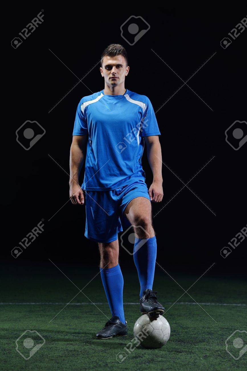 soccer player doing kick with ball on football stadium  field  isolated on black background Stock Photo - 23224763