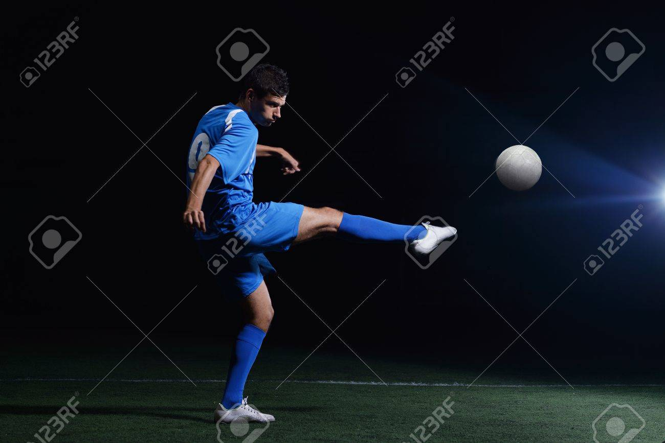 soccer player doing kick with ball on football stadium  field  isolated on black background Stock Photo - 16715095