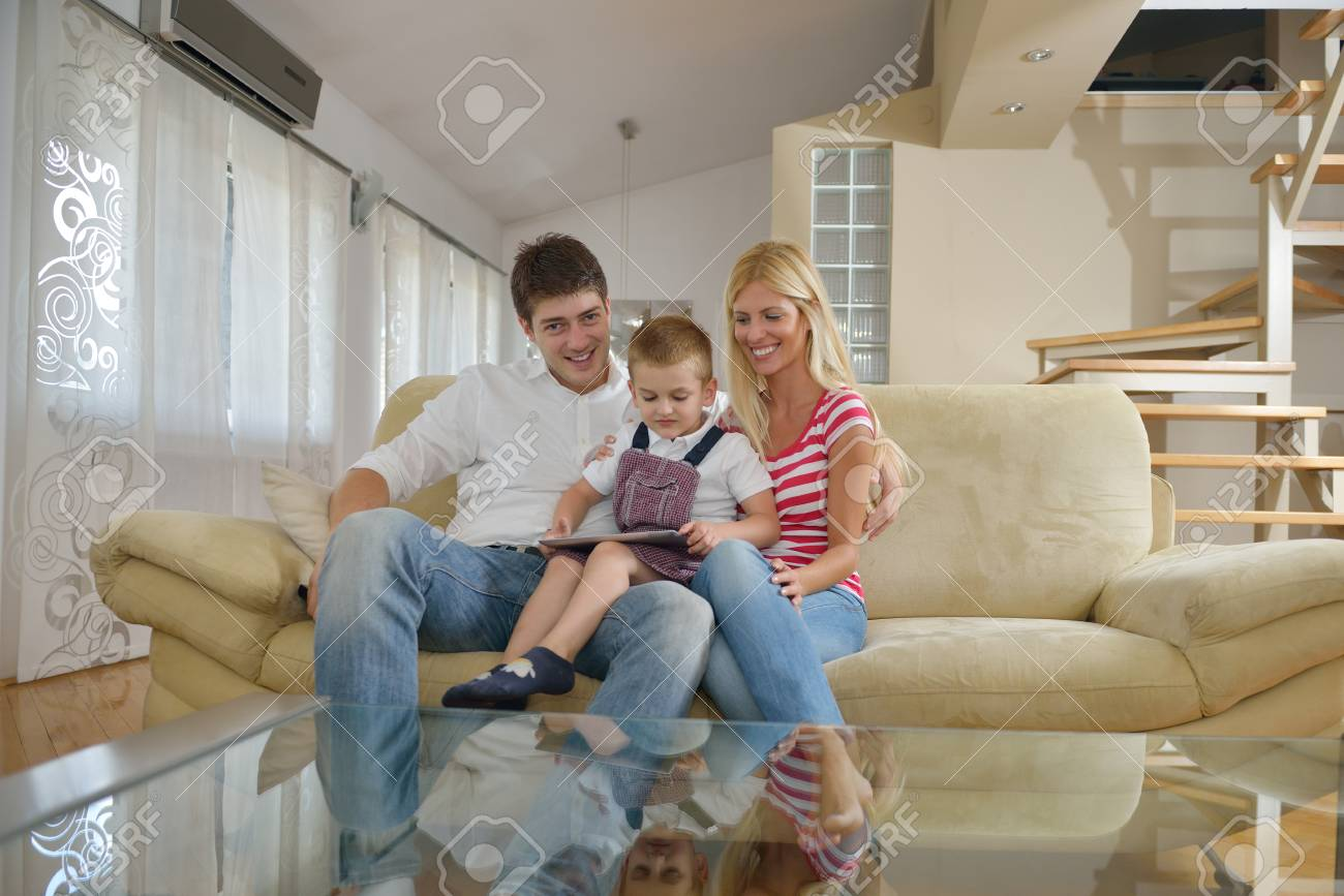 happy young family using tablet computer at modern  home for playing games and education Stock Photo - 25378827