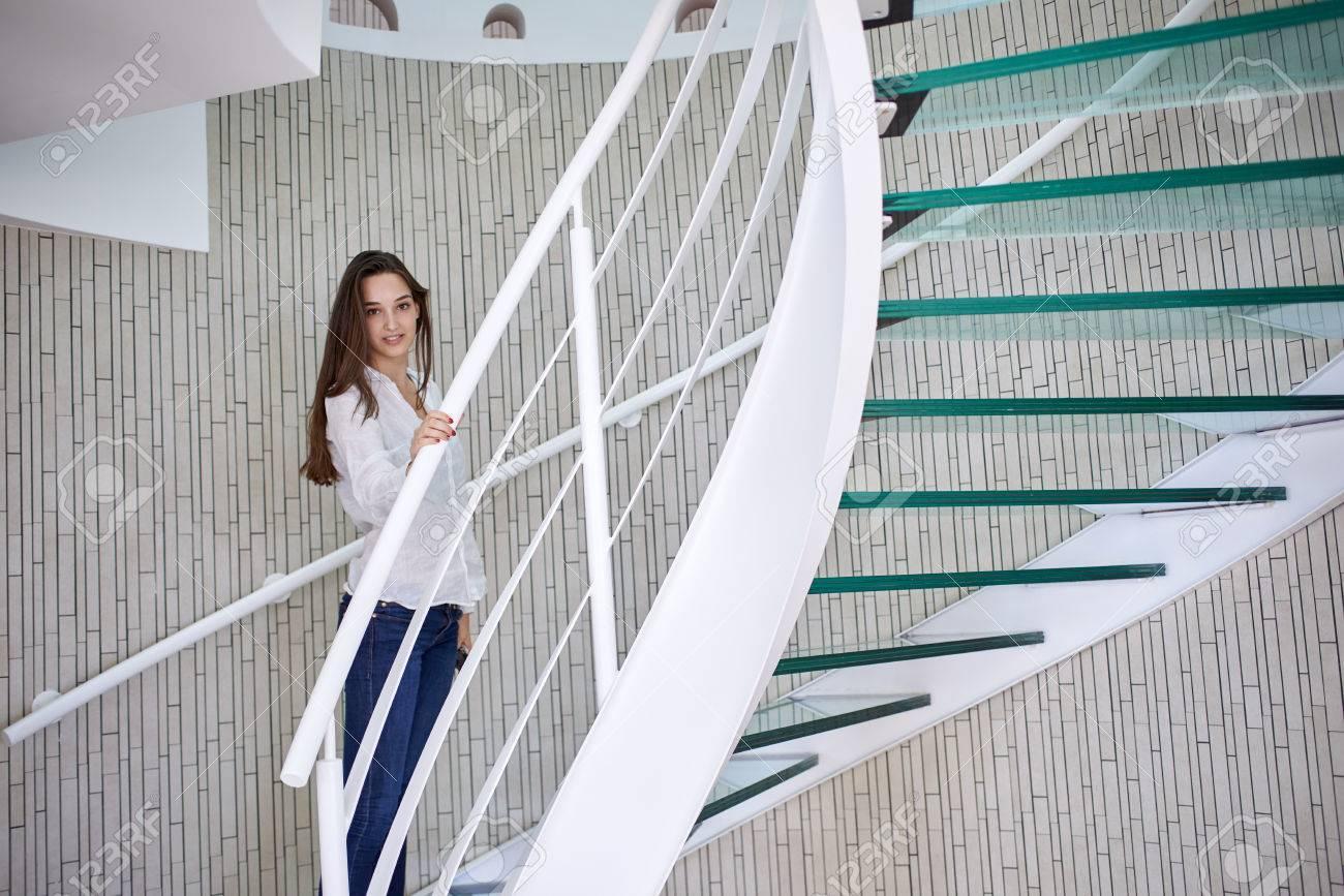 mujer joven que recorre en las escaleras de caracol en casa moderna en el interior foto