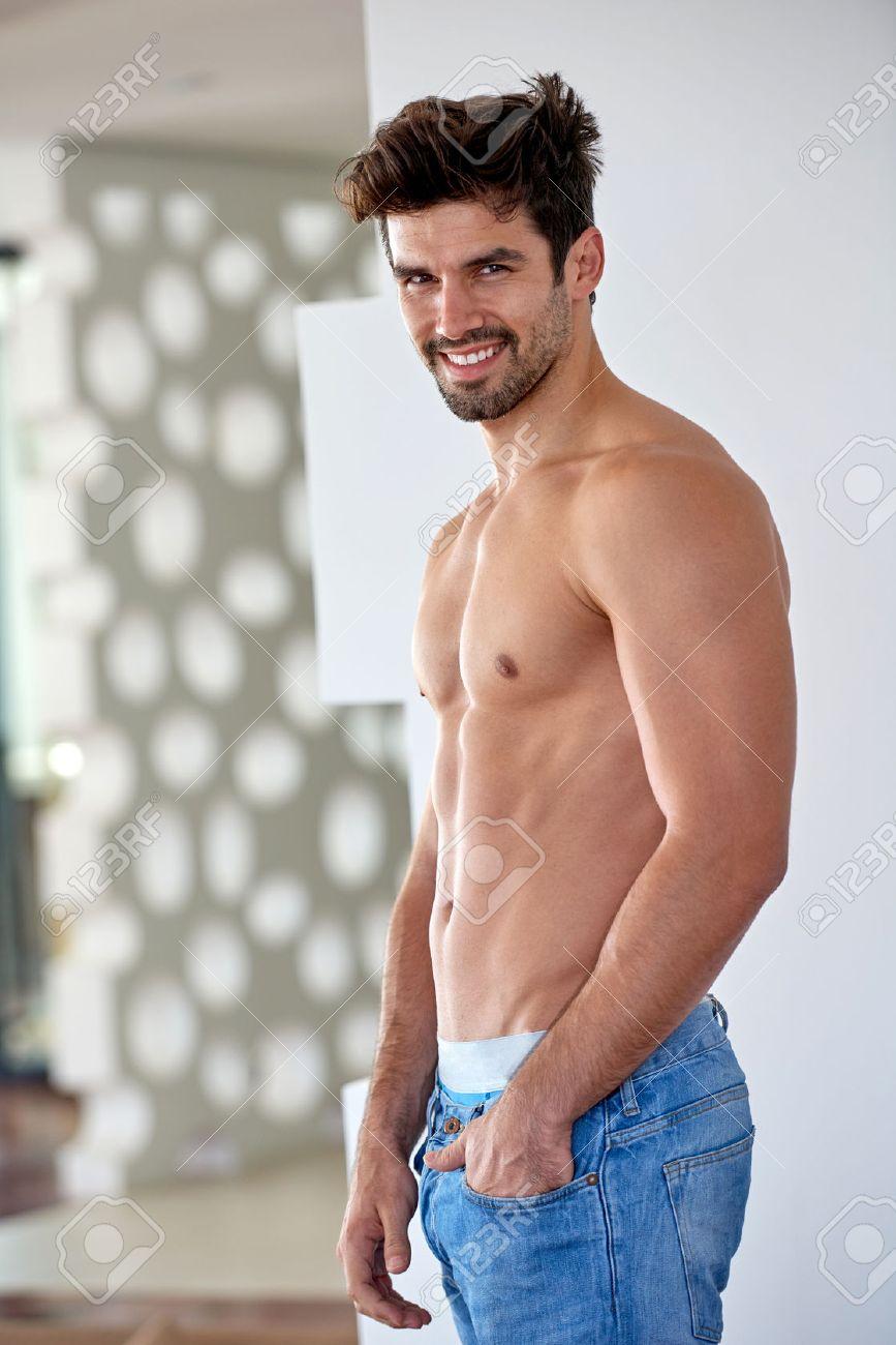 Beau Jeune Homme torse nu beau jeune homme en jeans posant à l'intérieur de la maison