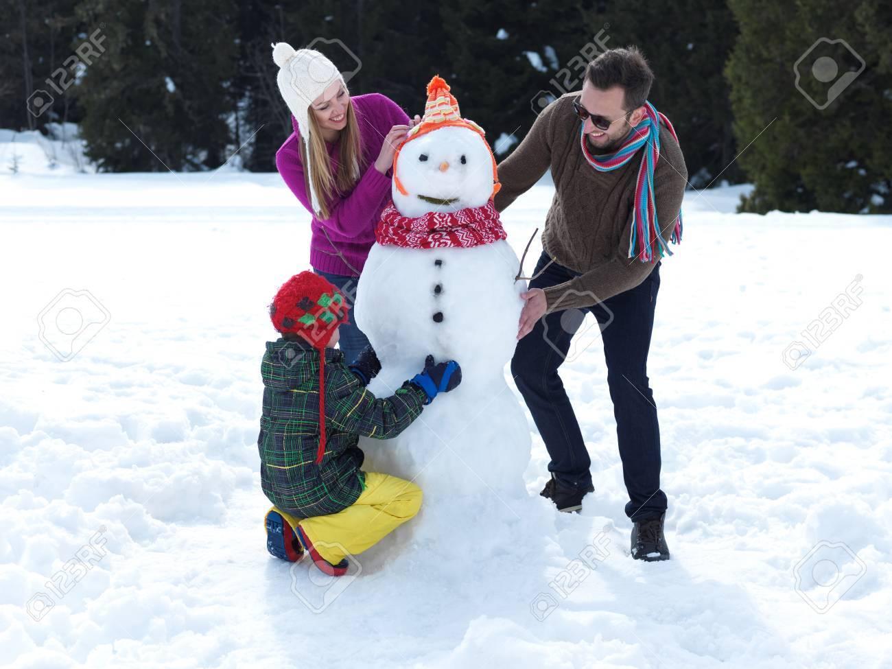 Joven Familia Feliz Jugando En La Nieve Fresca Y Haciendo Muñeco De Nieve En El Hermoso Día De Invierno Soleado Al Aire Libre En La Naturaleza Con El Bosque En Fondo Fotos