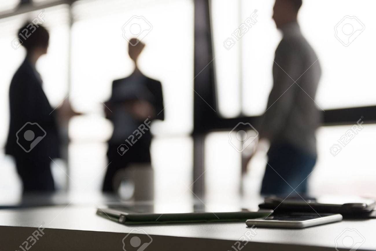 Close up of smart phone and tablet computer at office meeting room. Business people group interacting in background. - 55664948
