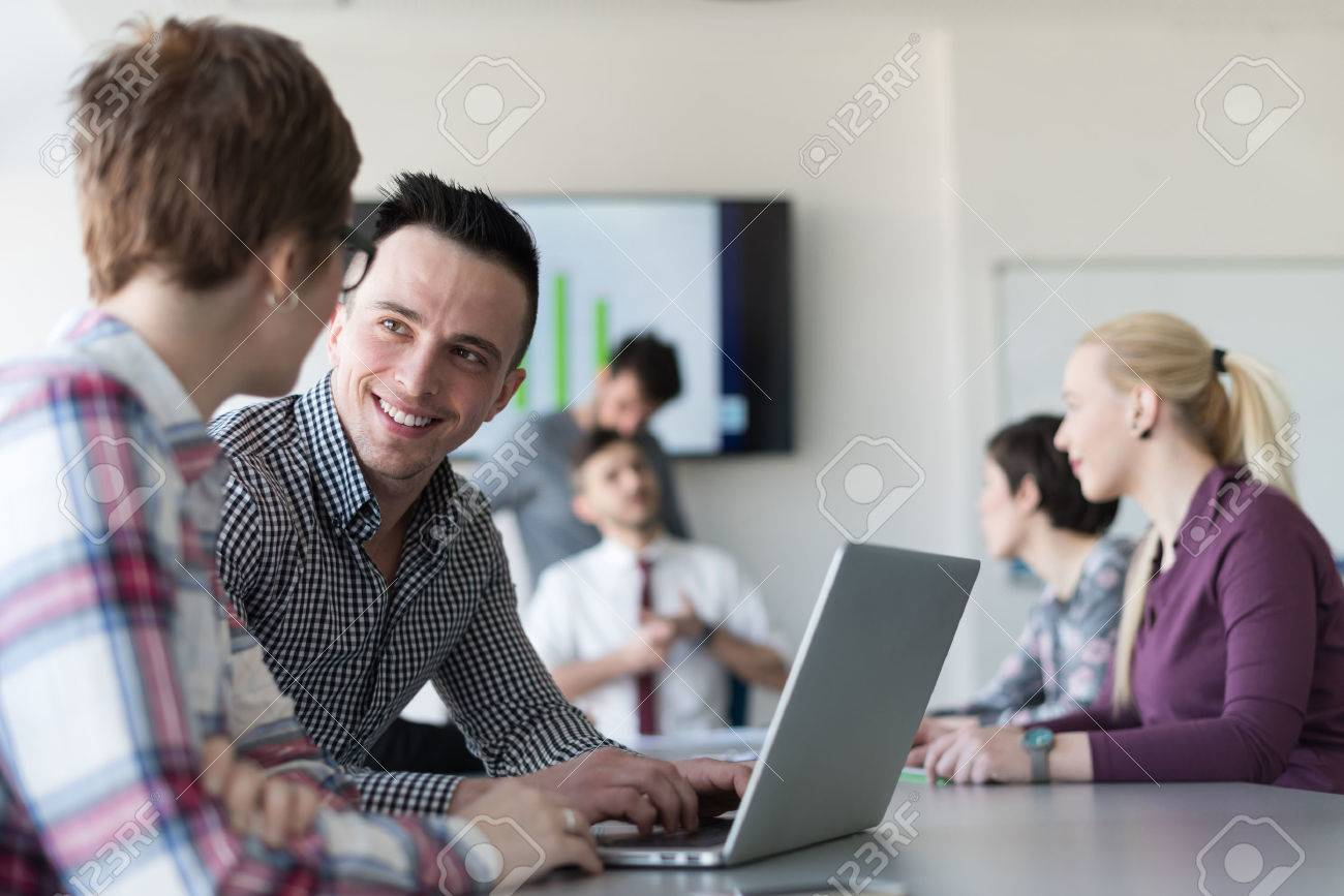 young startup business people, couple working on laptop computer, businesspeople group on meeting in background at office interior - 57007505