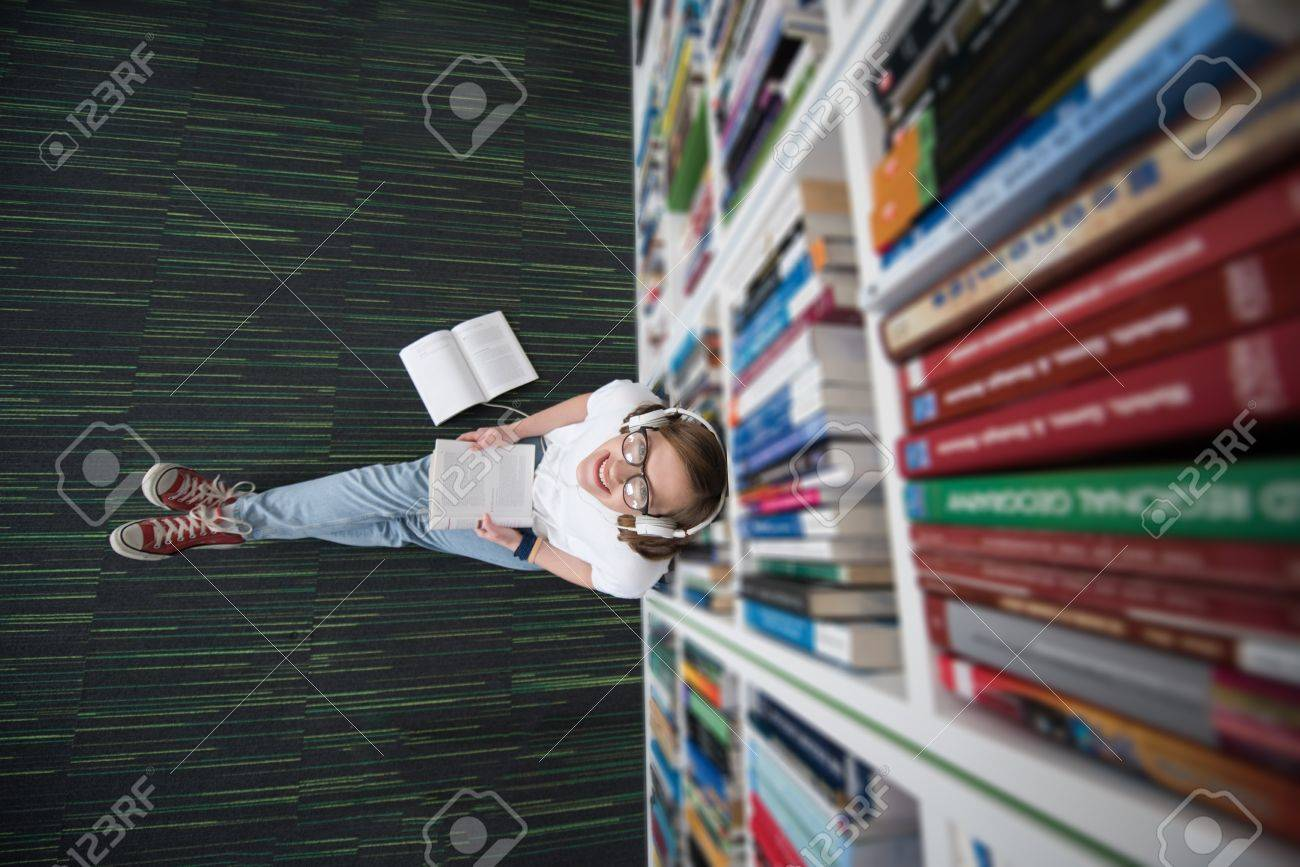 female student study in school library, using tablet and searching for information's on internet. Listening music and lessons on white headphones - 57689154