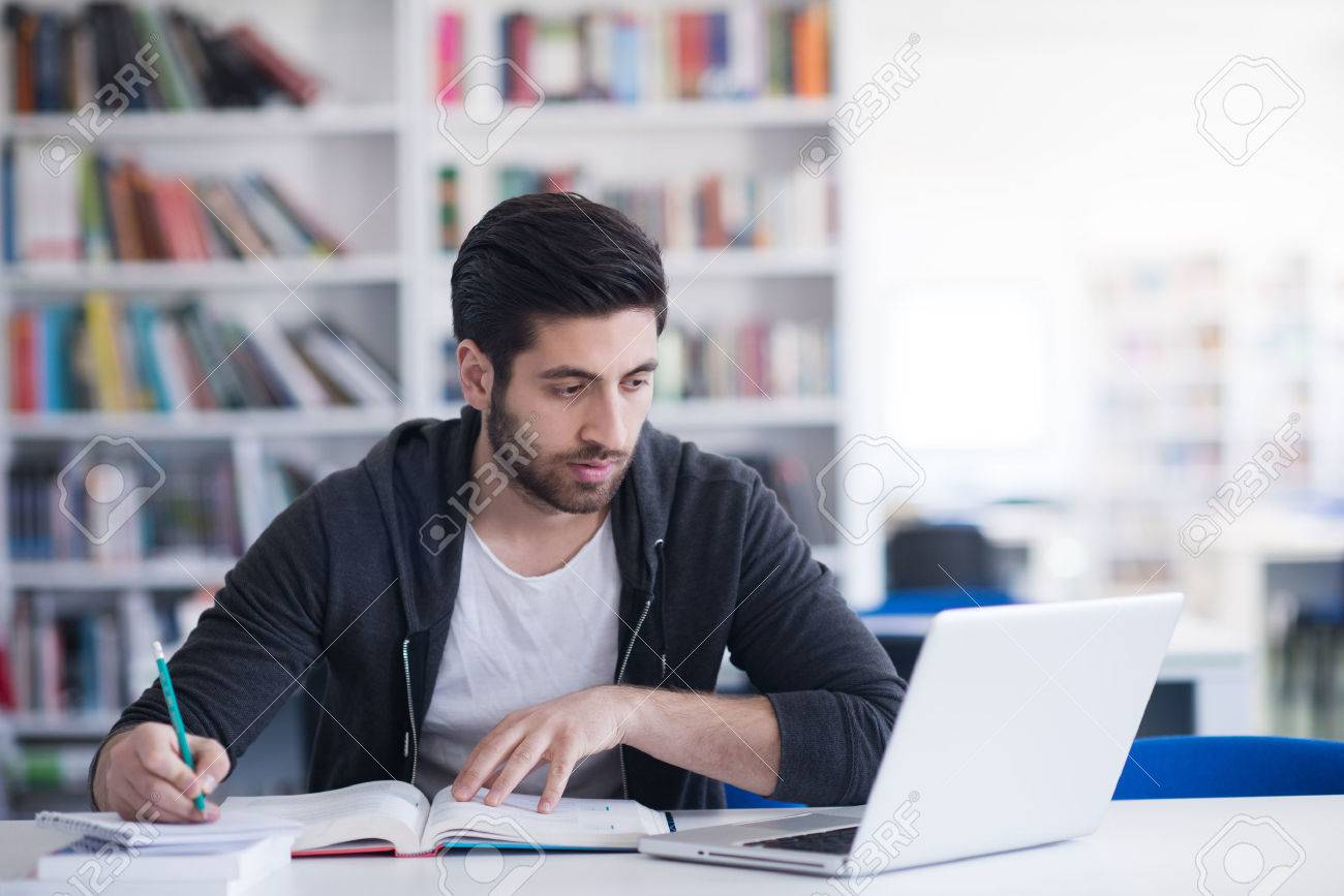 student preparing exam and learning lessons in school library, making research on laptop and browse internet - 57798413
