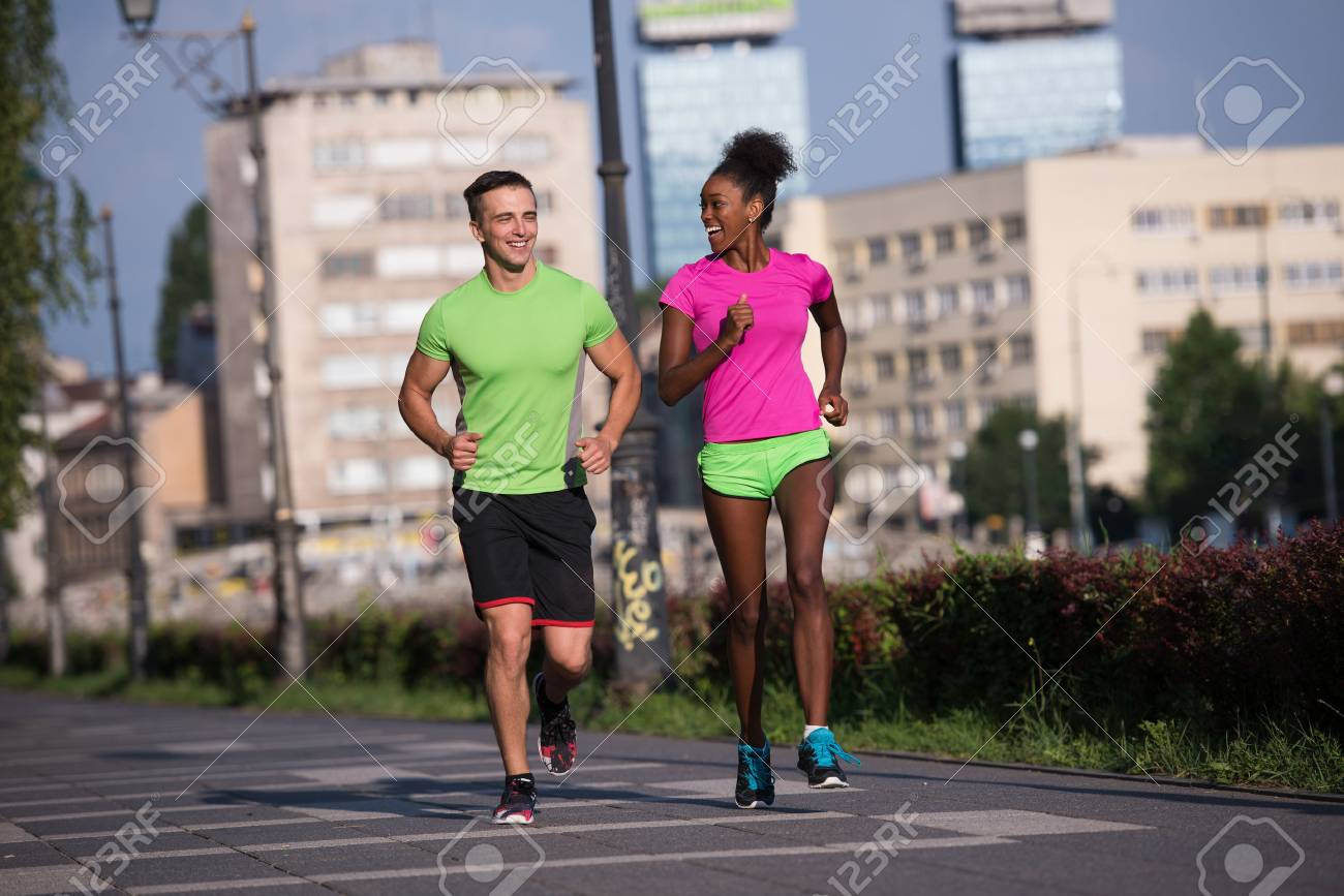 healthy young multiethnic couple jogging in the city on a sunny summer day - 67136460