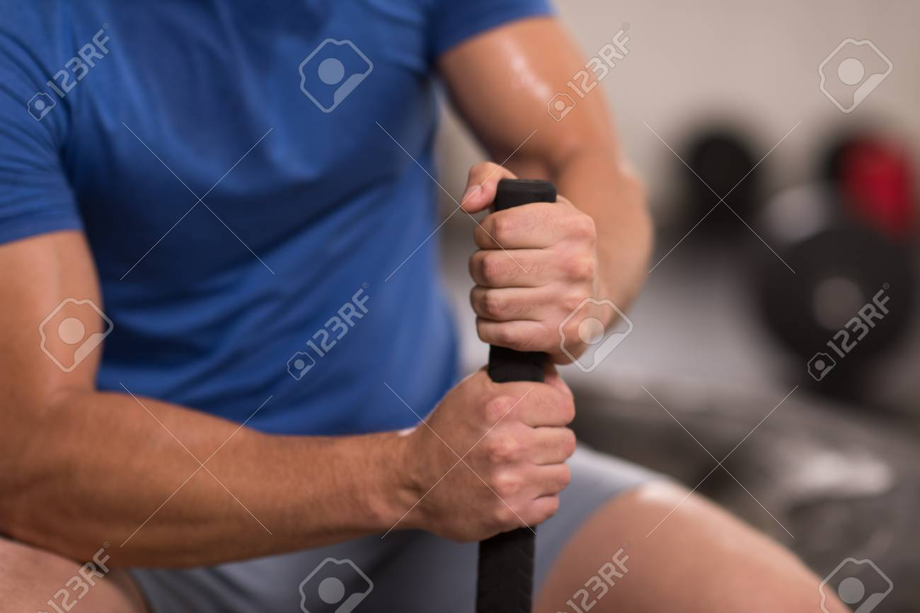 Young Muscular Man After Workout At Gym With Hammer And Tractor