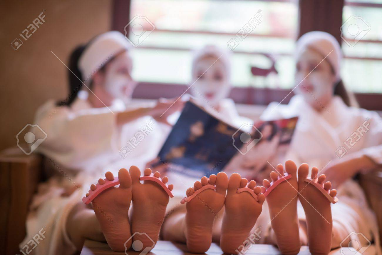 group of famale friends in spa have fun, celebrate bachelorette party with face mask - 73377587