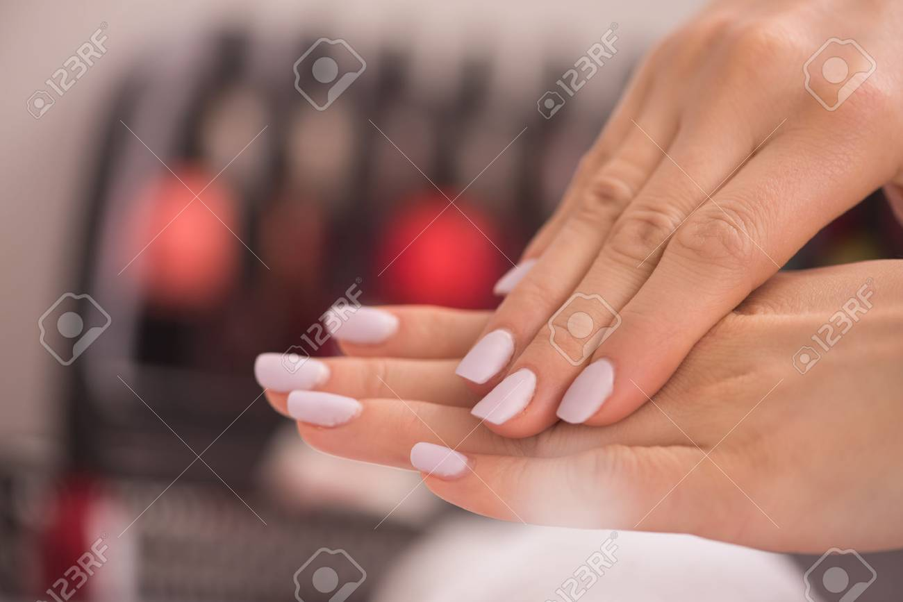 Beautiful fingers with french manicure on the towel. Manicure in a beauty salon. - 74110651