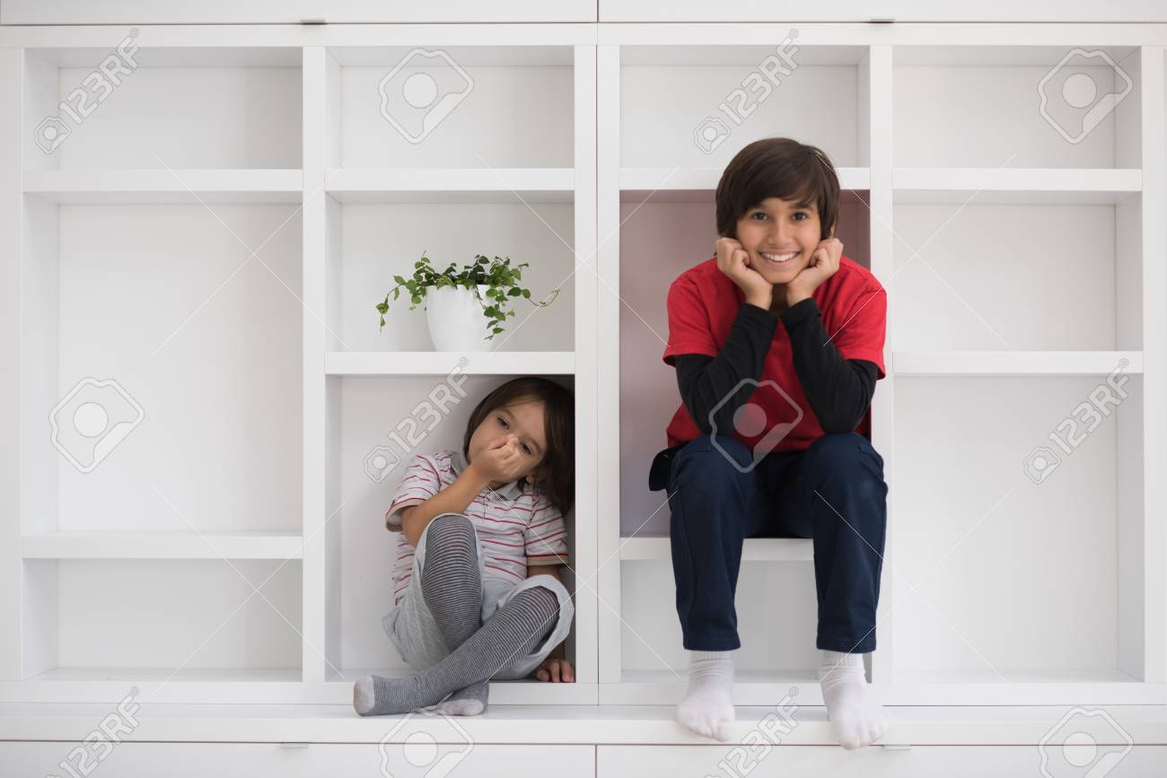 happy young boys are having fun while posing on a shelf in a new modern home - 74117908