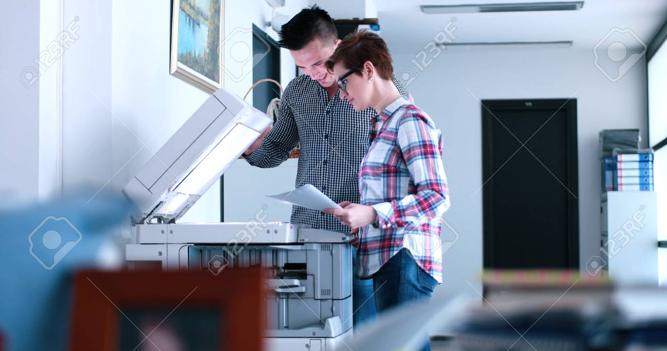 Young Beautiful Woman with assistant Making Copies Of Files In The Copy Machine - 76533225