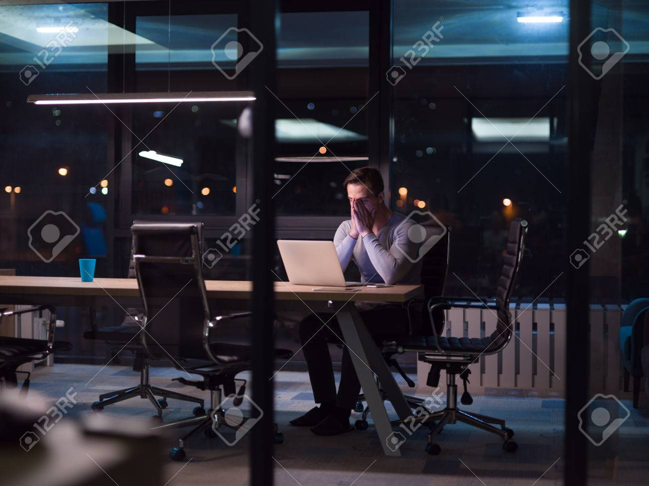Young man working on laptop at night in dark office. The designer works in the later time. - 80575259