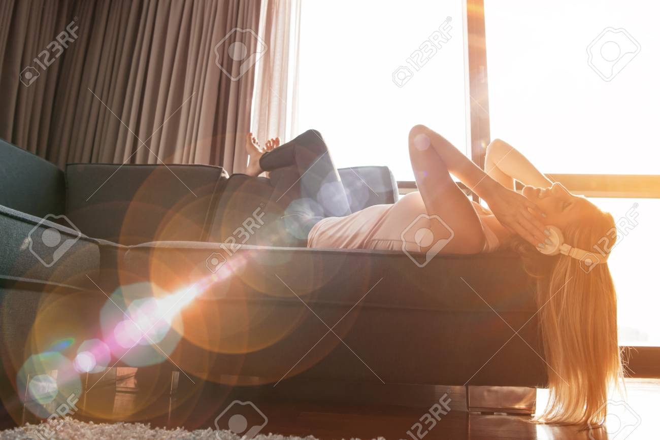 woman listening to music with sun flare coming from window of apartment - 80699608