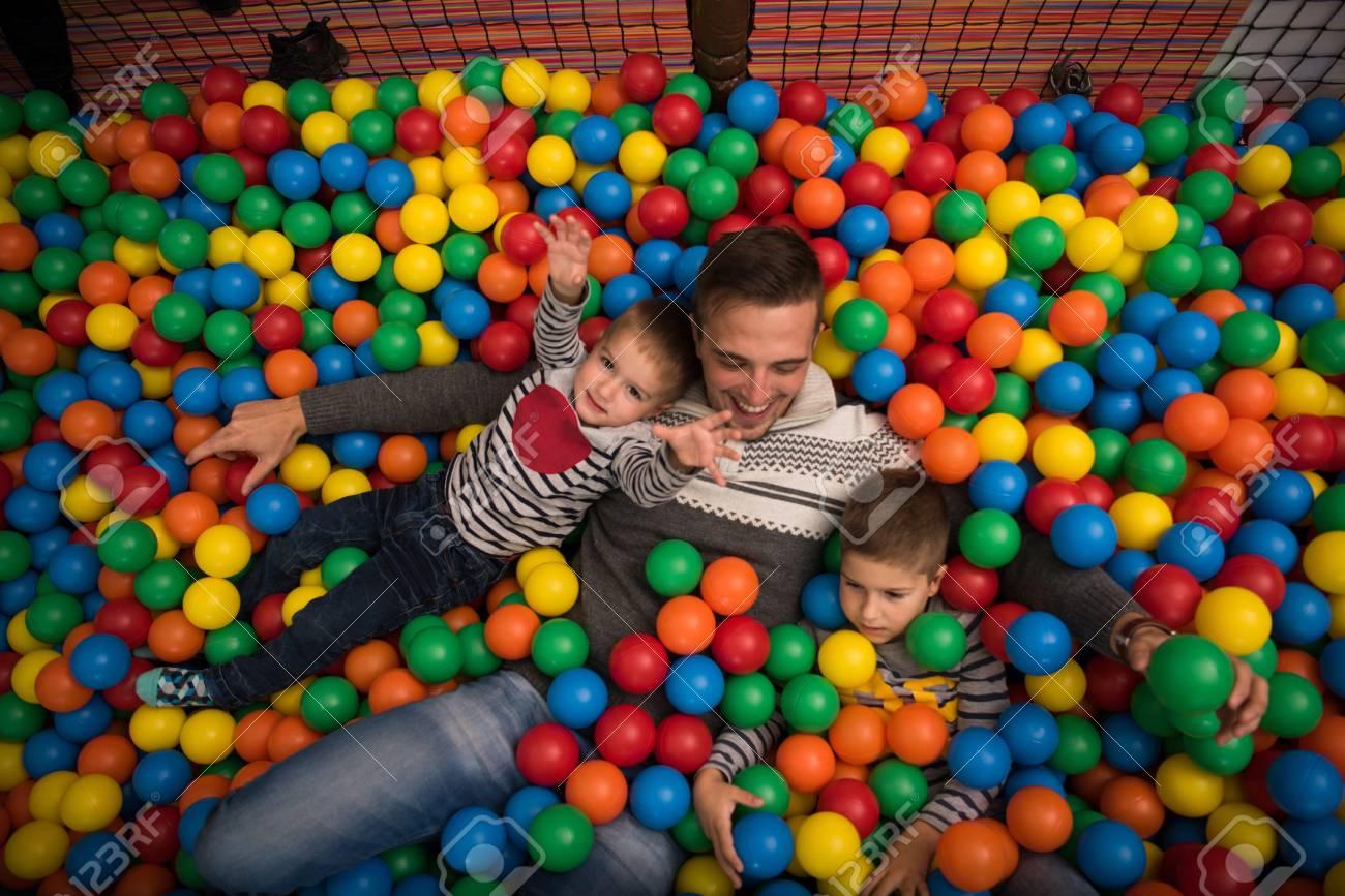 Stanza Dei Giochi Bambini : Il giovane papà gioca con i bambini allo stagno con le palle