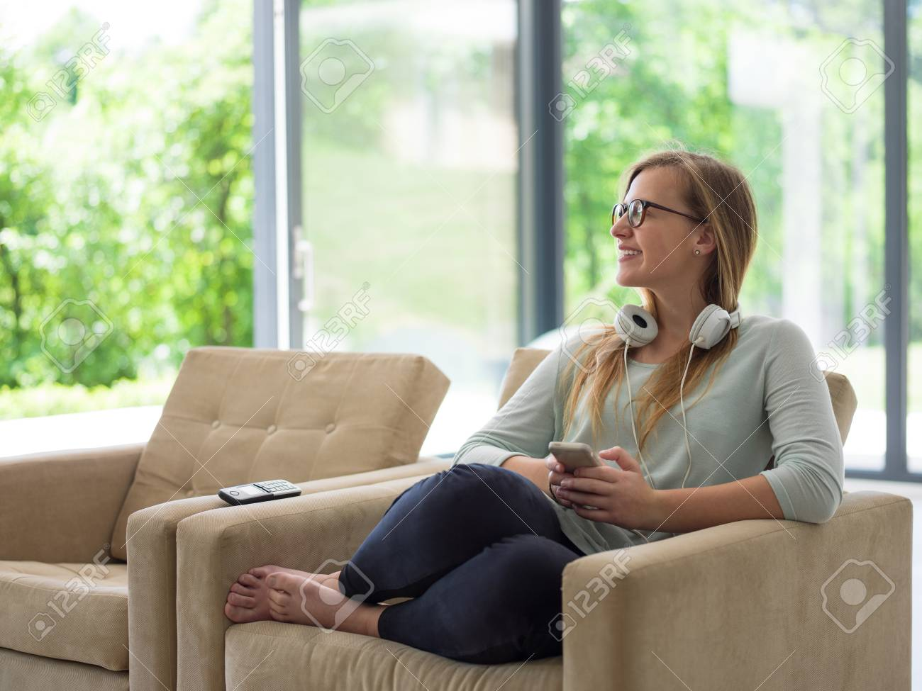 Stock Photo   Young Happy Woman Sitting On Sofa And Using Mobile Phone At Luxury  Home