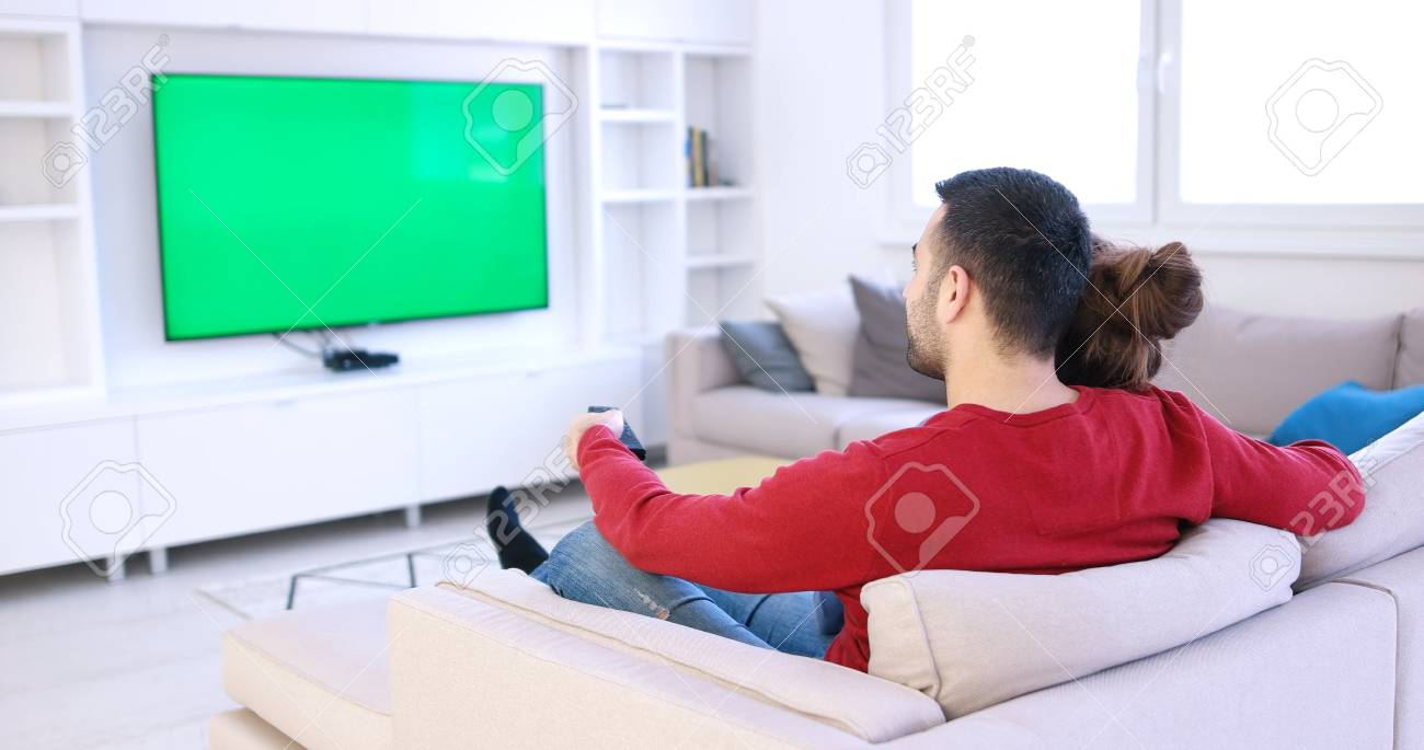 Young couple on the sofa watching television together in their luxury home - 87128829