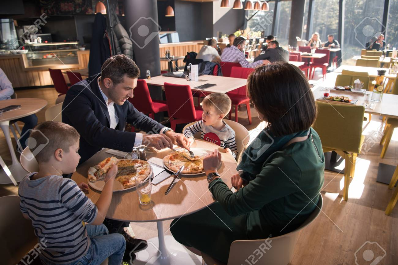 Young parents enjoying lunch time with their children at a luxury restaurant - 82630251