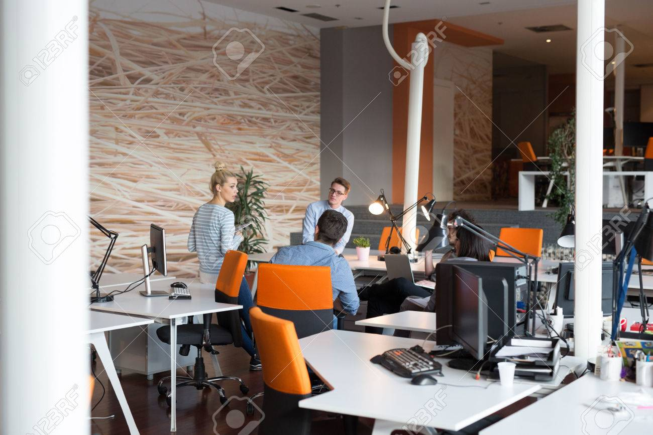 Group of a young business people discussing business plan in the office - 83107214
