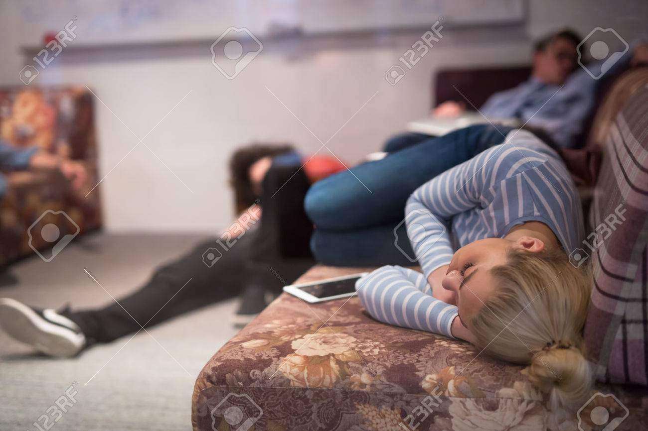group of young casual software developer sleeping on sofa during
