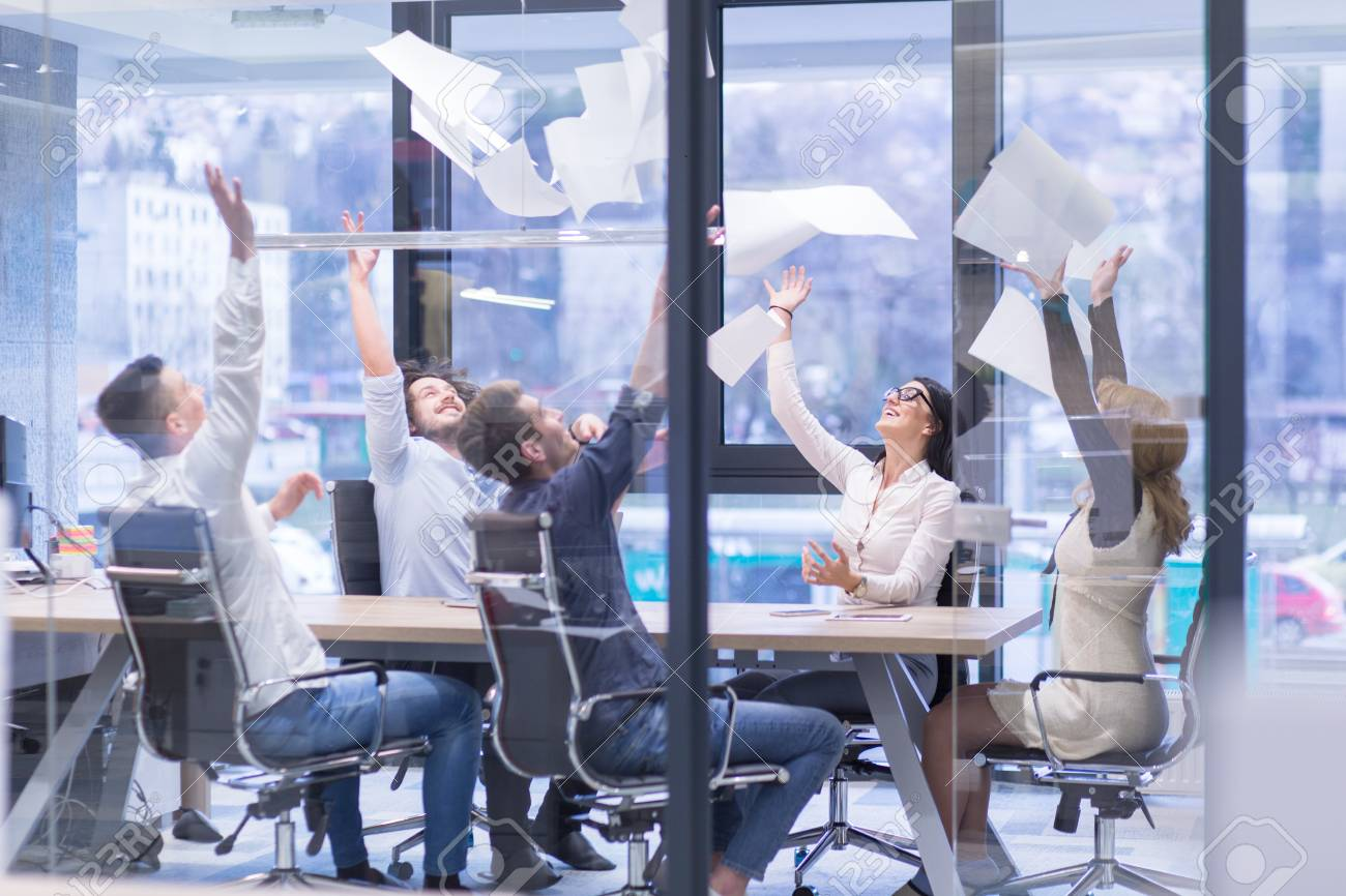 Group of young business people throwing documents and looking happy while celebrating success at their working places in startup office - 89477128