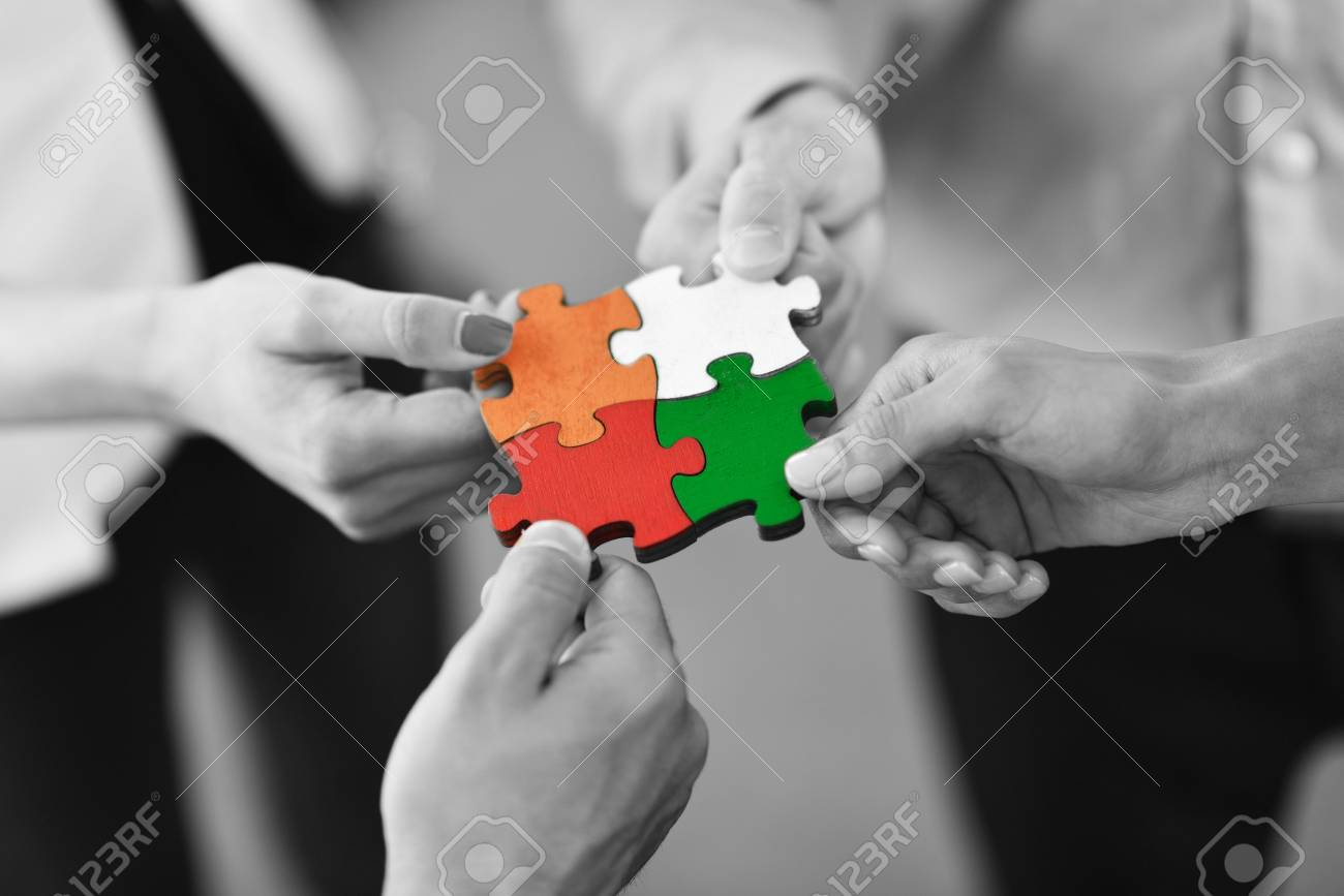 Group of business people assembling jigsaw puzzle and represent team support and help concept - 94128748
