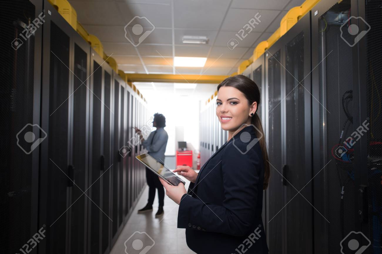 Female IT engineer working on a tablet computer in server room at modern data center - 94491442