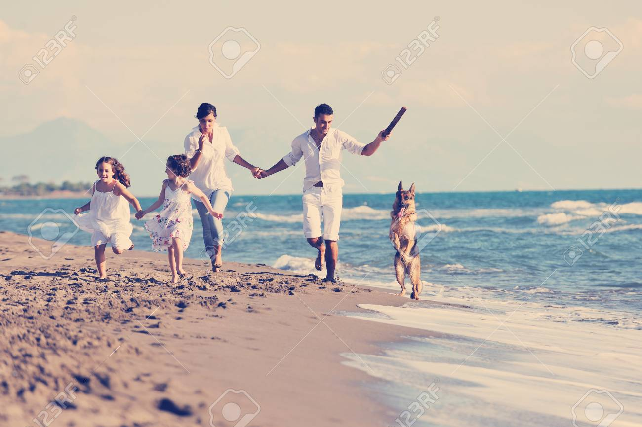 happy young family in white clothing have fun and play with beautiful dog at vacations on beautiful beach - 98432131