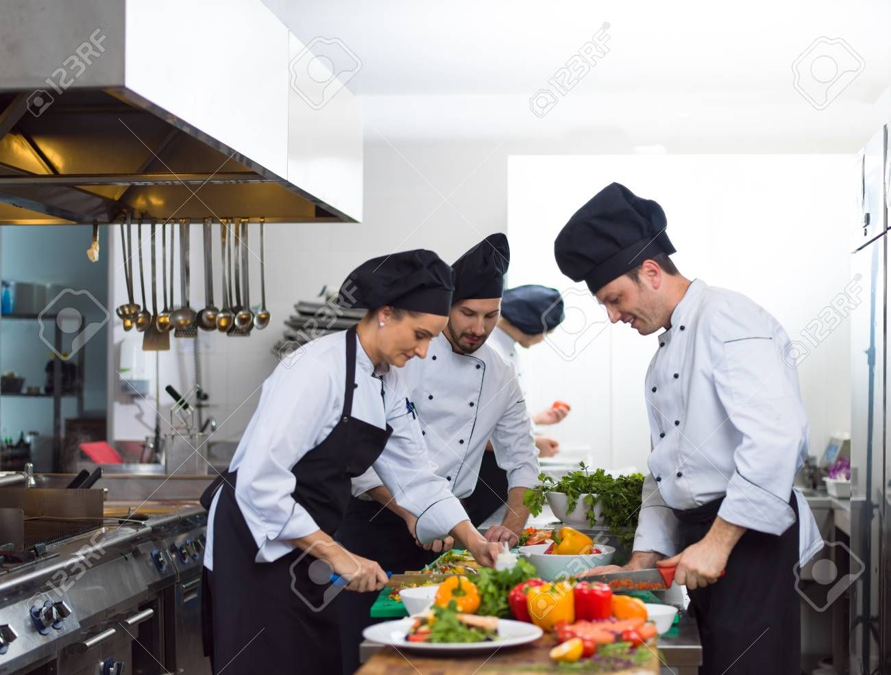 Professional team cooks and chefs preparing meals at busy hotel or restaurant kitchen - 101426840