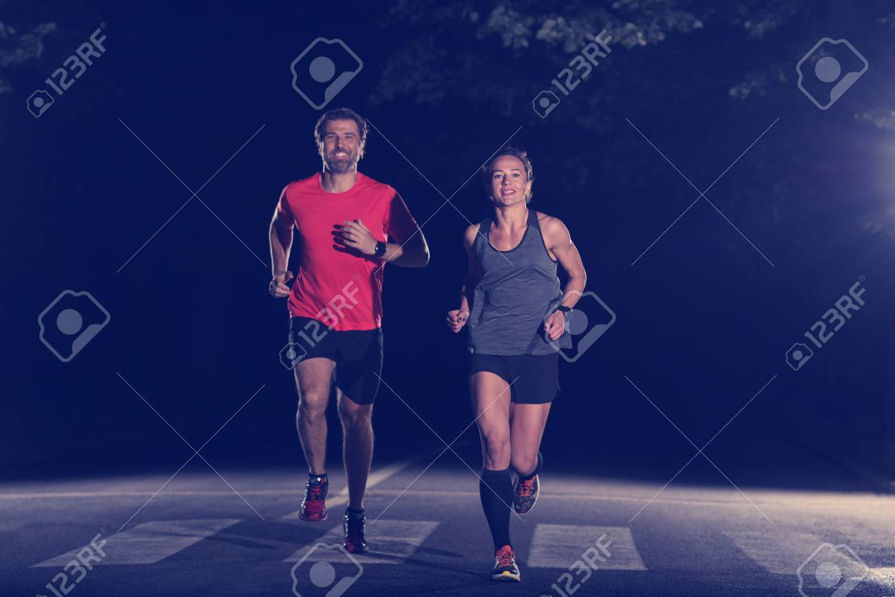 group of healthy people jogging in city park, runners team at night training - 107002795