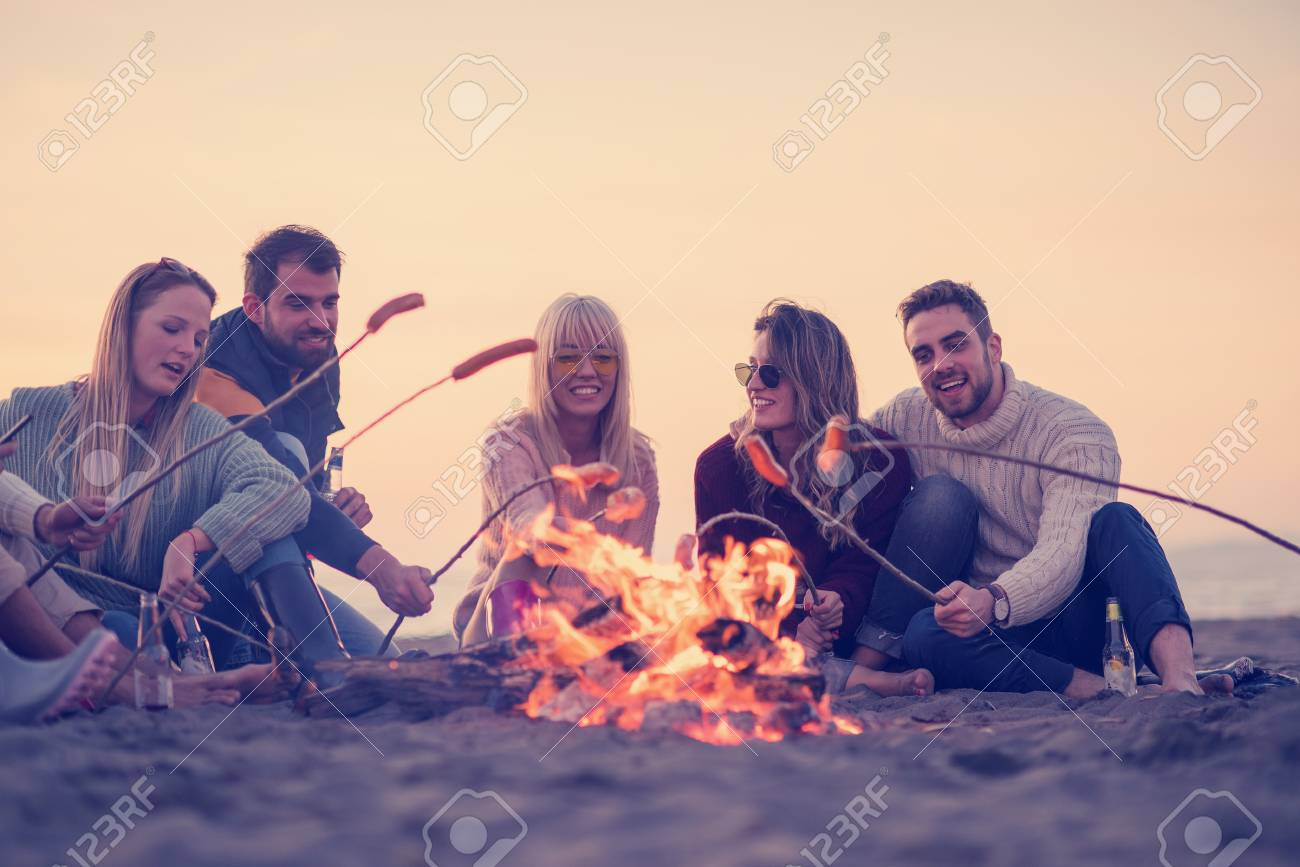 Group of young friends sitting by the fire at autumn beach, grilling sausages and drinking beer, talking and having fun - 107290336