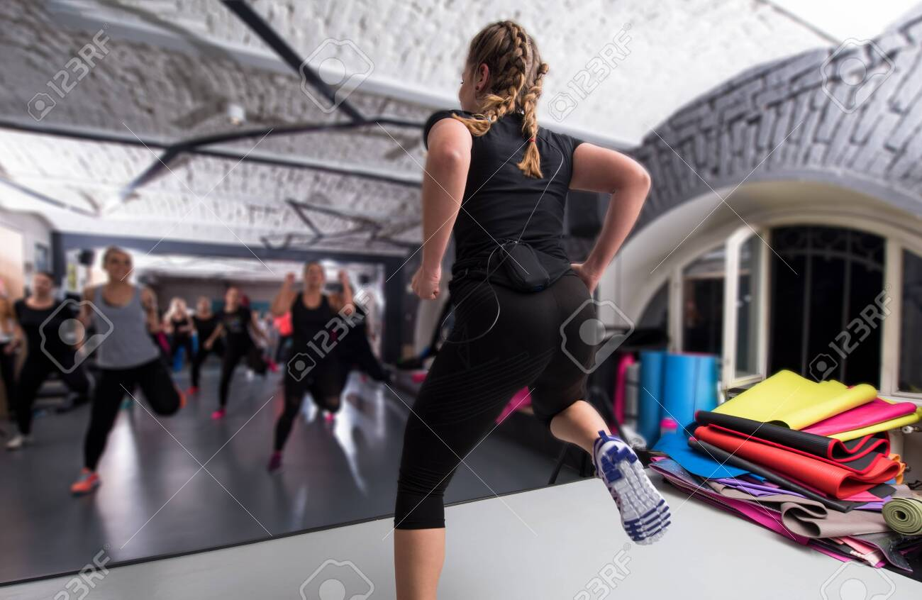 A group of young healthy sporty women working out with instructor doing aerobics exercises in a fitness studio fitness, sport, training, gym and lifestyle concept - 122847759