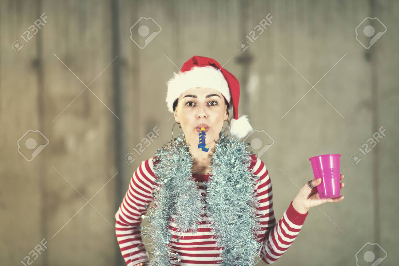 young happy casual business woman wearing a red hat and blowing party whistle while dancing during new years party in front of concrete wall - 126590774