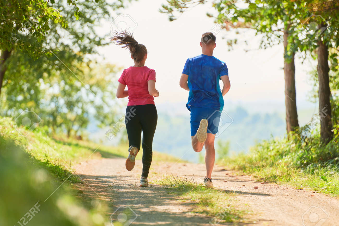 couple enjoying in a healthy lifestyle while jogging on a country road - 166294813