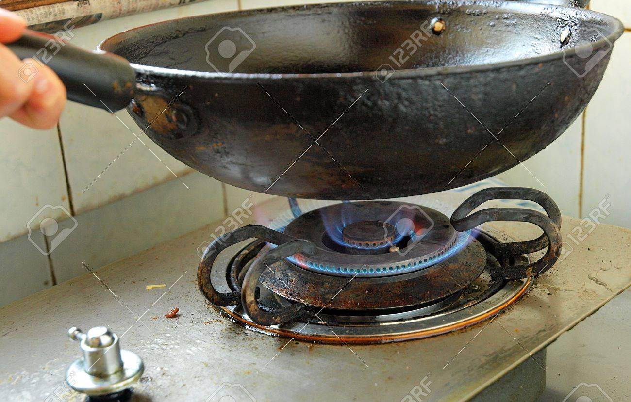 Hand met een wok boven open vuur in een chinese keuken royalty ...