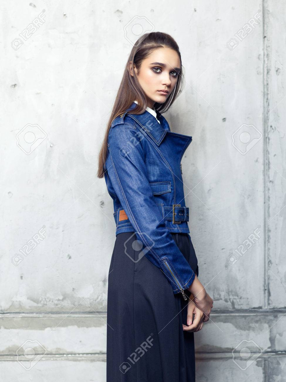 7222d67231 Fashion model wearing denim jacket and long black skirt posing in studio on  concrete wall Stock