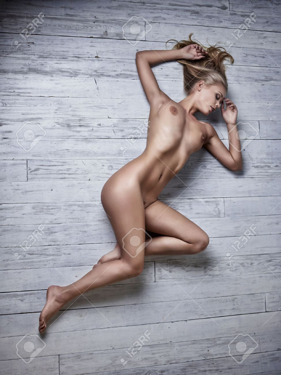 9/9/18-9/15/18 62966566-sexy-nude-woman-laying-down-on-a-white-wooden-floor-artistic-photo-