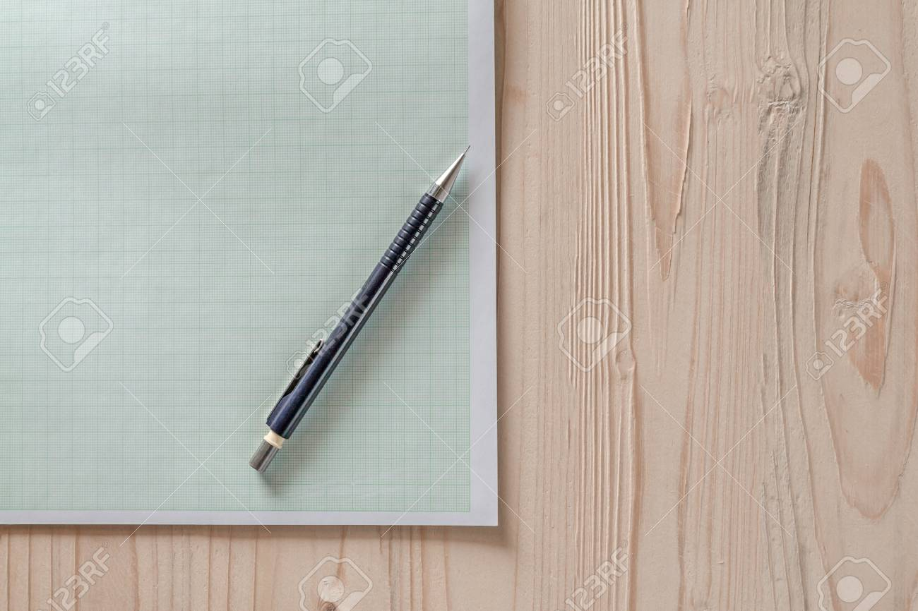 drafting paper or graph paper with pencil on wooden desk close