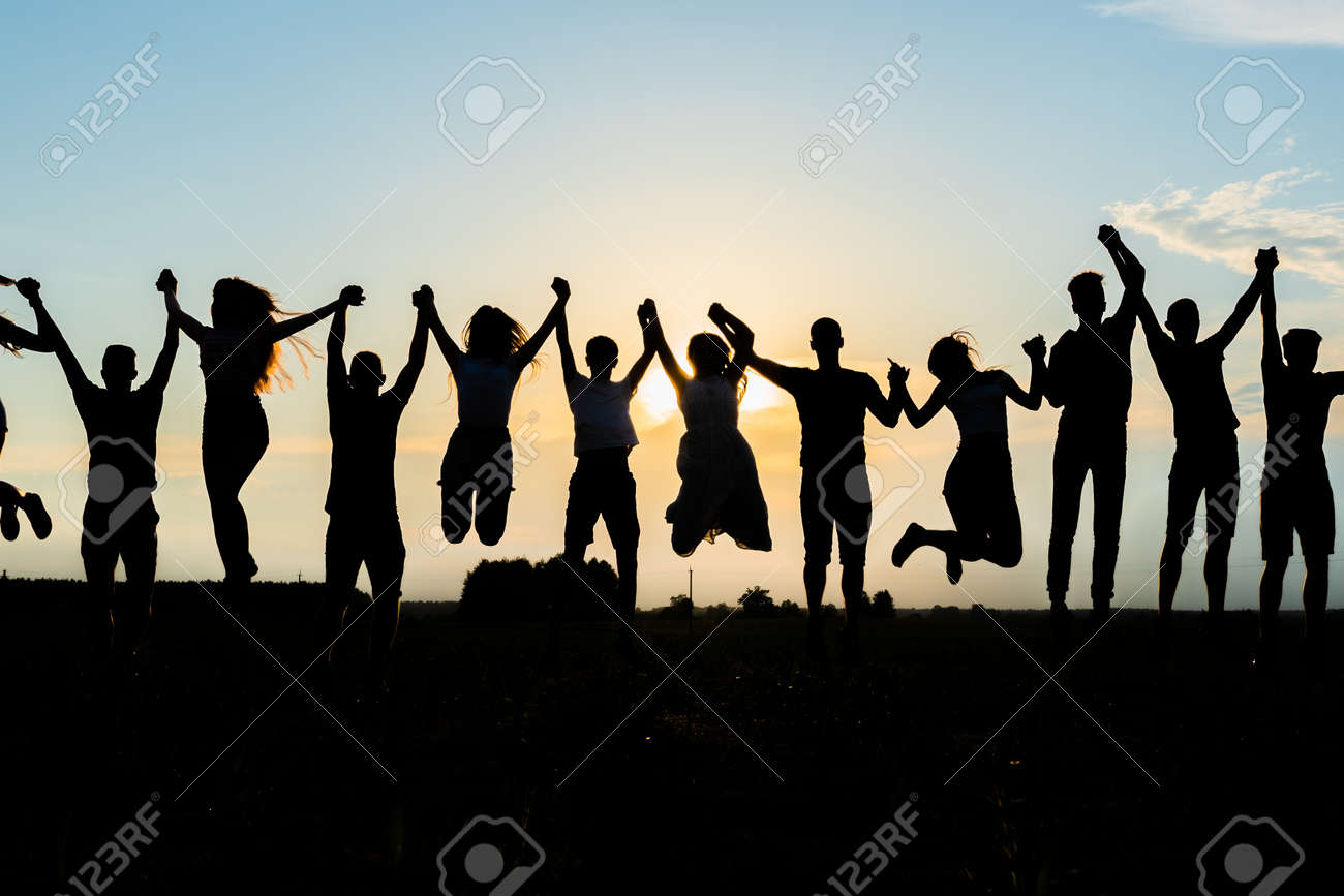 Silhouettes of jumping friends on a sunset background. - 151789085