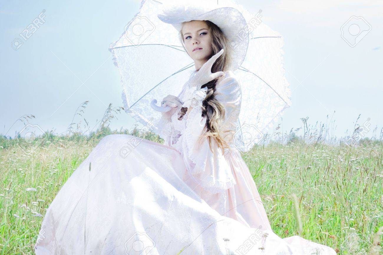 Beautiful woman in vintage dress sitting in a field Stock Photo - 7525754
