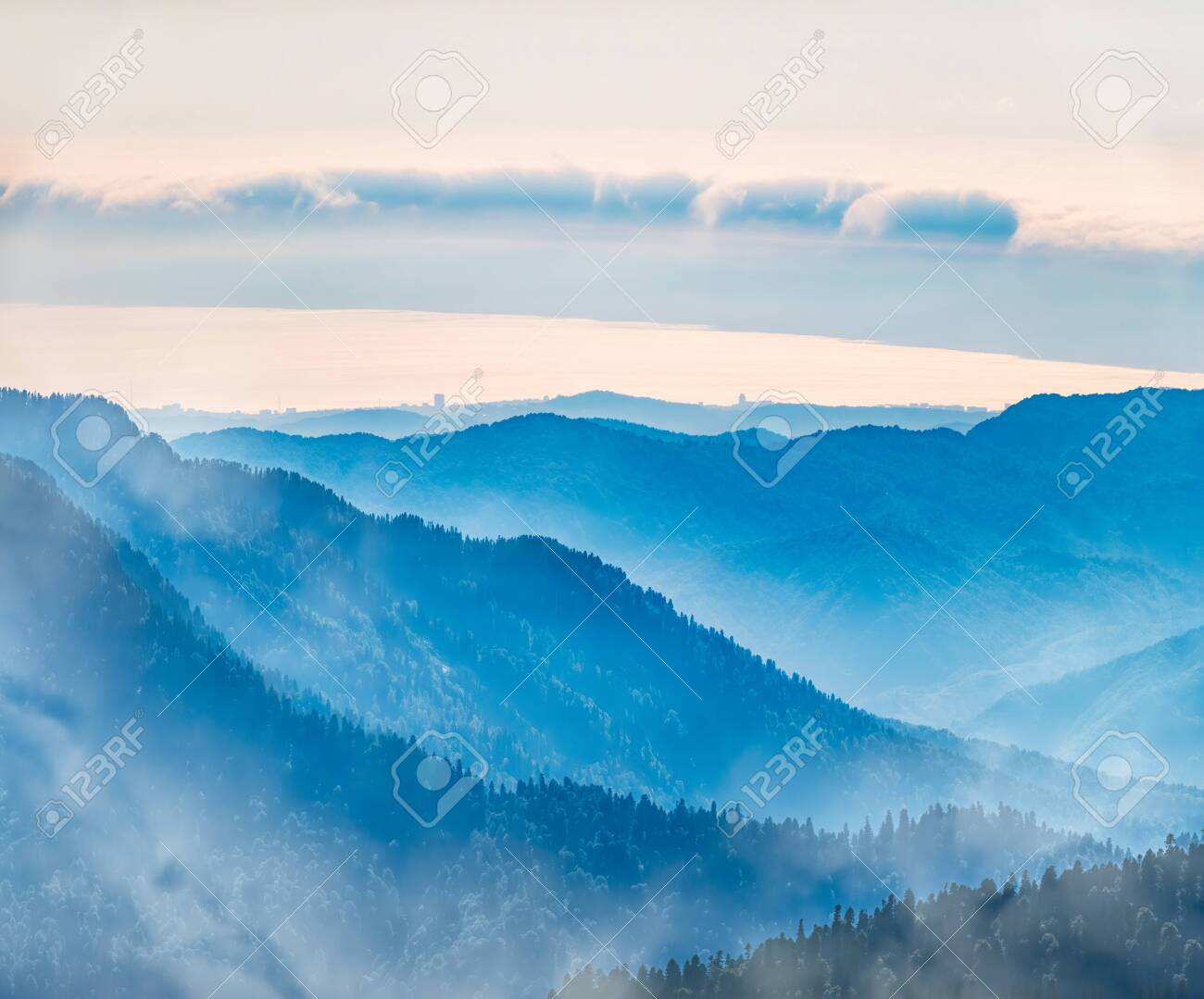 Green mountain slope. Layers of mountains in the haze during sunset. Multilayered misty nountains. Krasnaya Polyana, Sochi, Russia. - 144096804