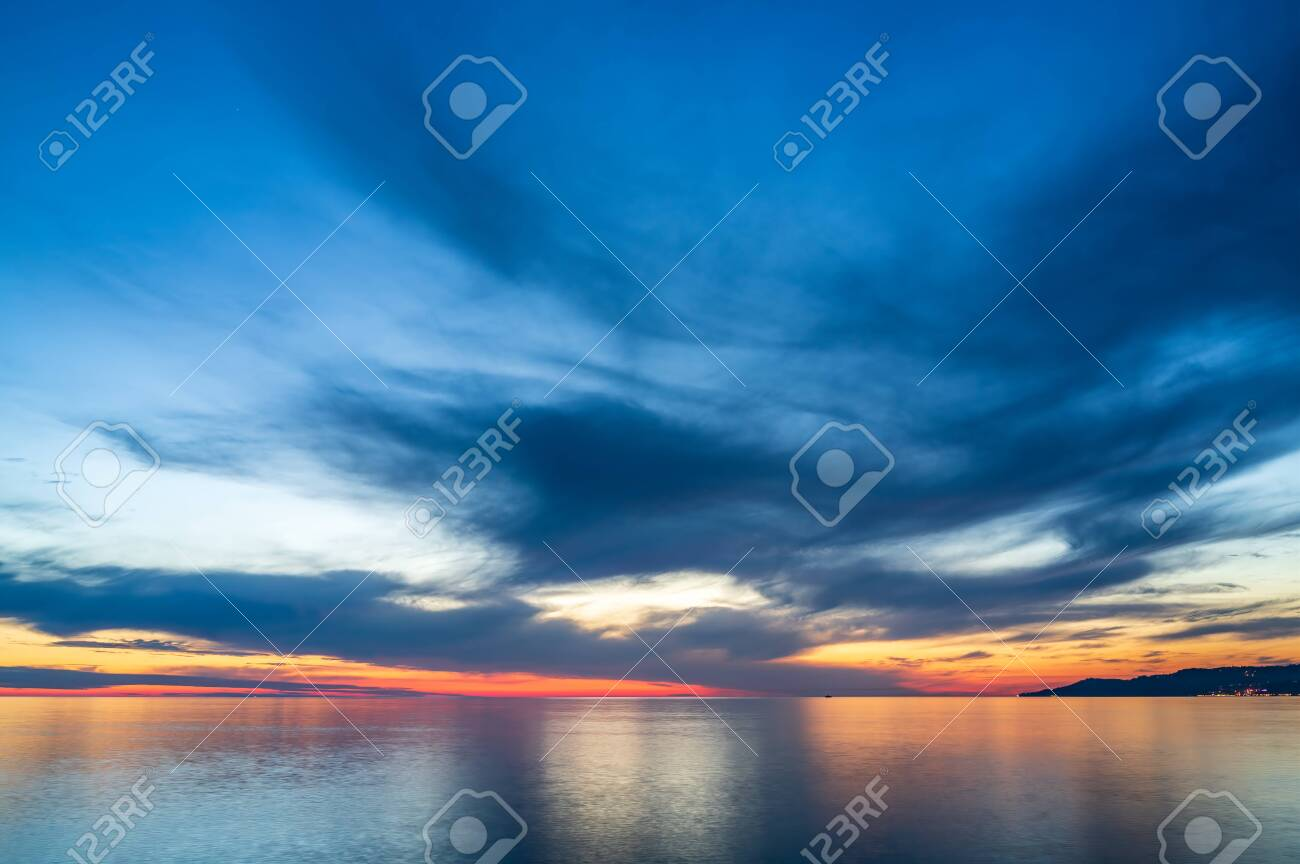 Beautiful orange sunset over the sea in a cloudy sky. - 154280393