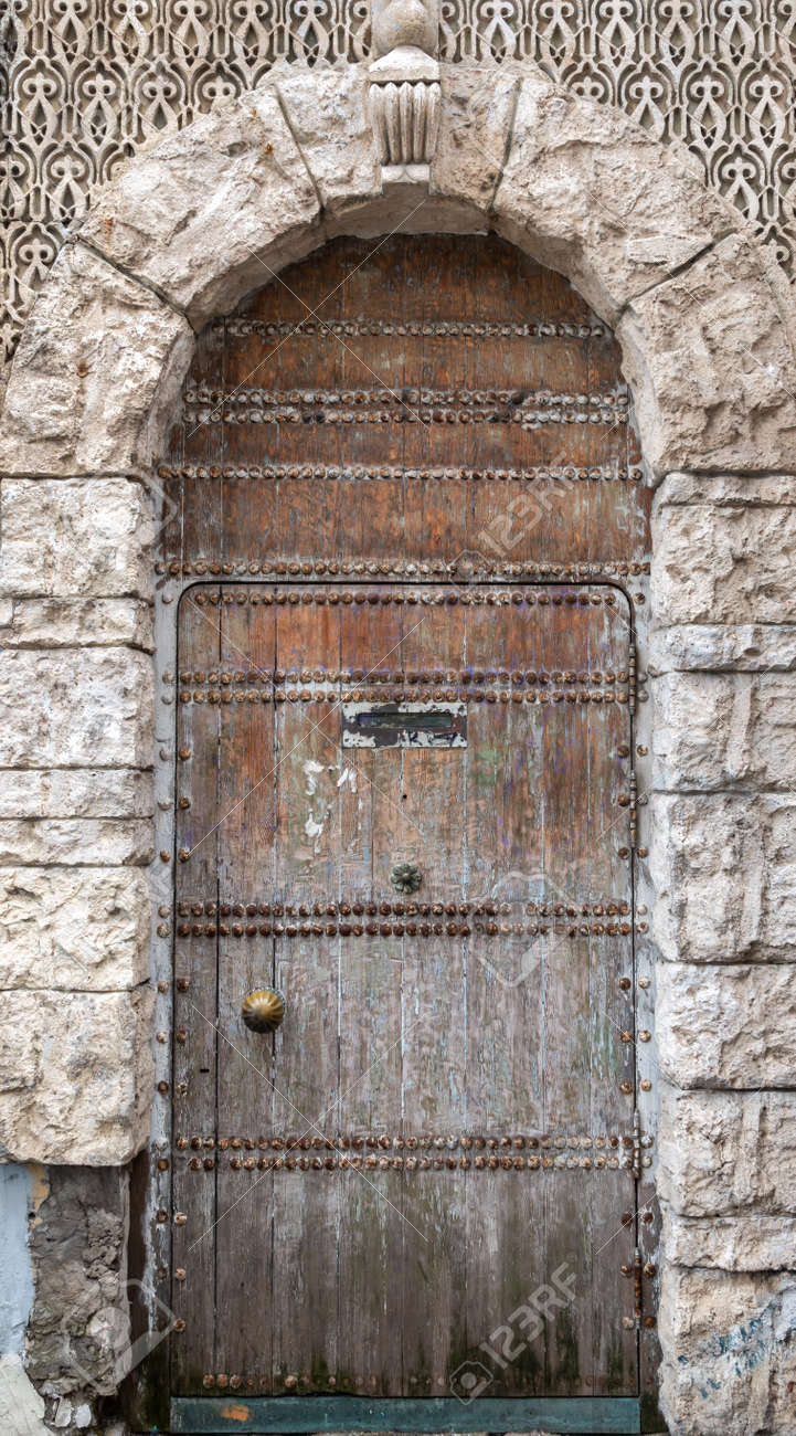 Ancient stone wall with a gate in the old castle. Wooden gate of a medieval castle - 170095174