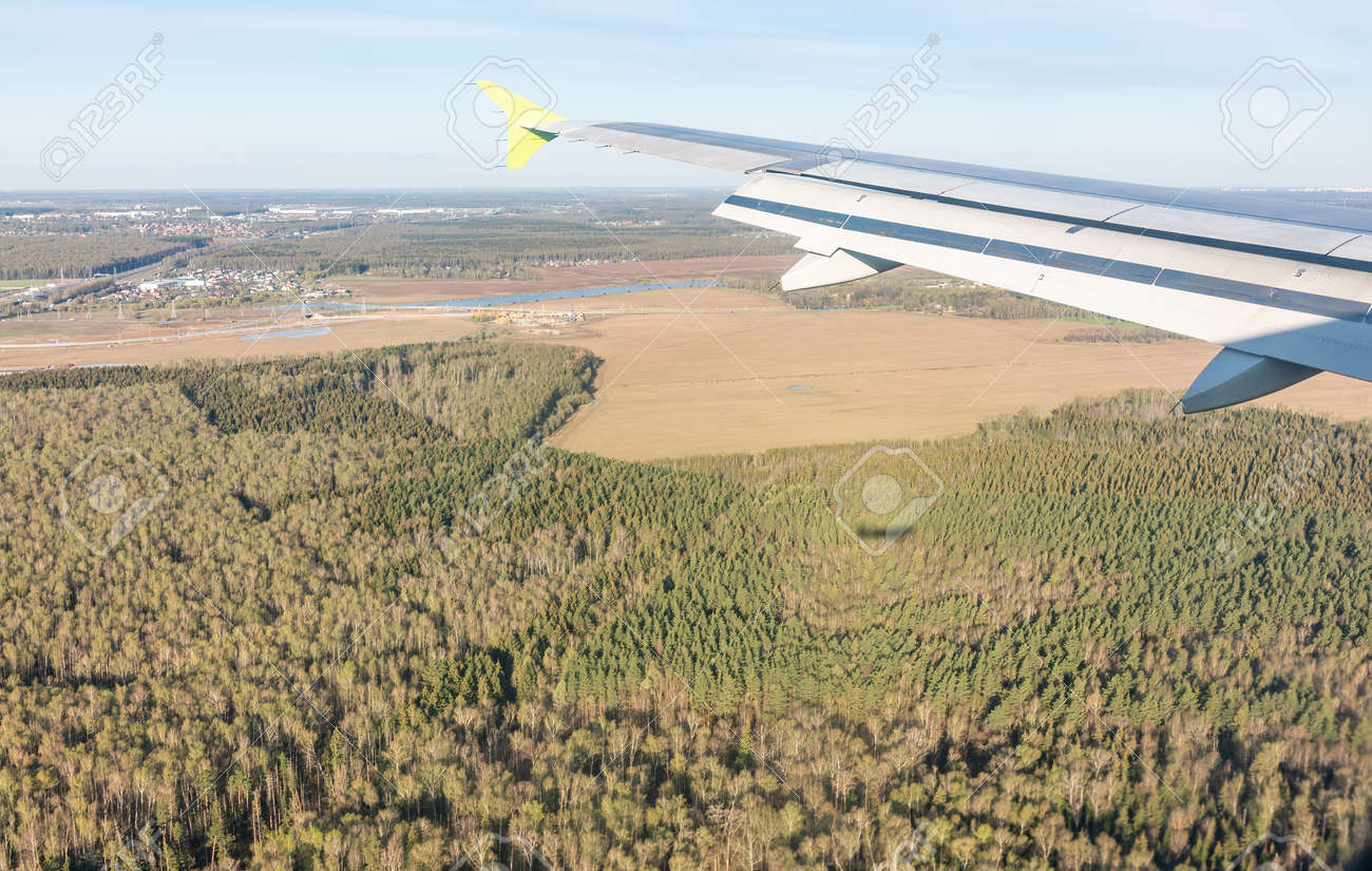 View of airplane wing, blue skies and the land during landing in Moscow, Russia. Airplane window view. Earth and sky as seen through window of an airplane. - 170095175