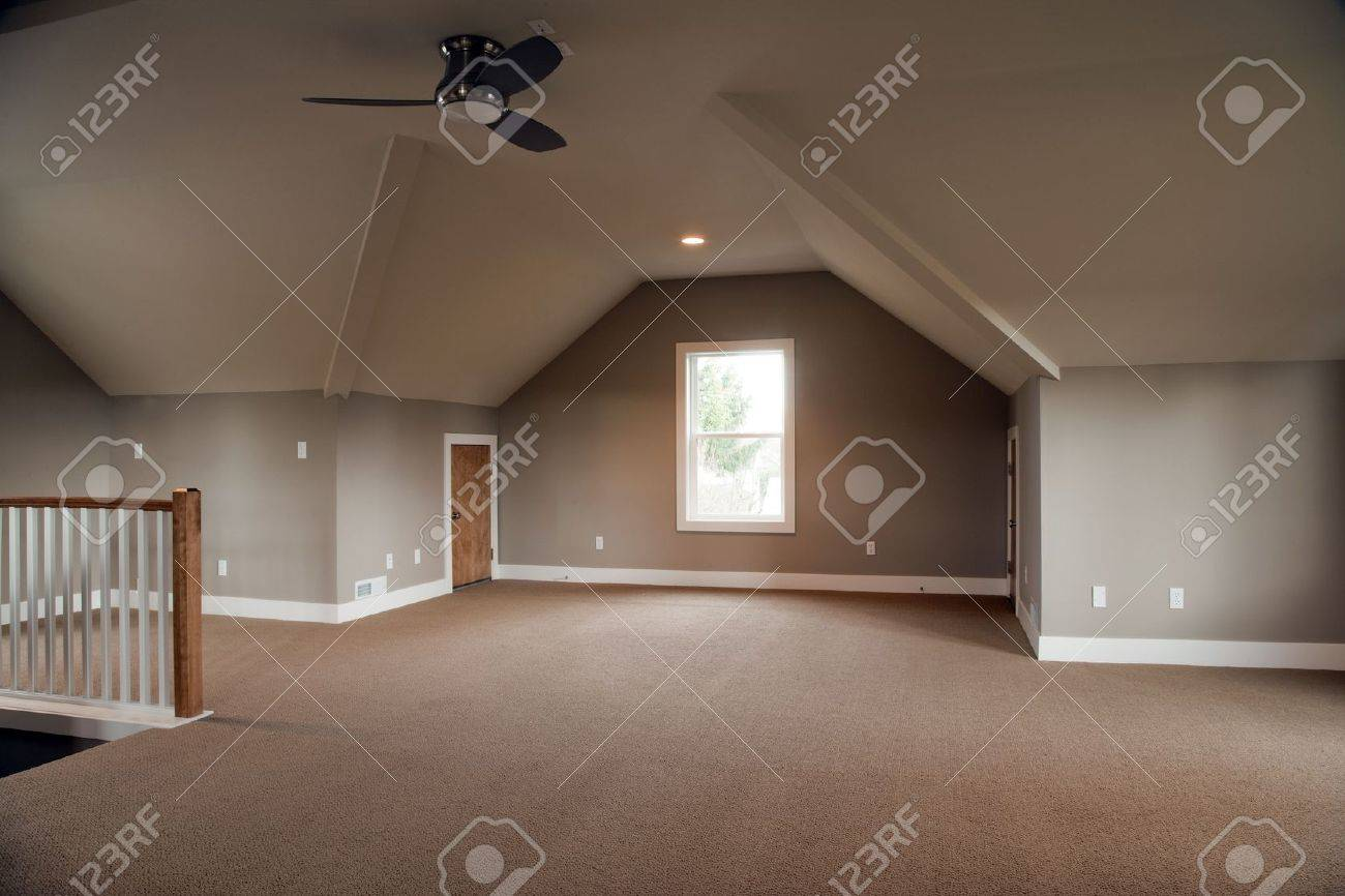 Unfinished attic of a home. It is empty except for a ceiling fan in the center of the room. Horizontal shot. Stock Photo - 6431558
