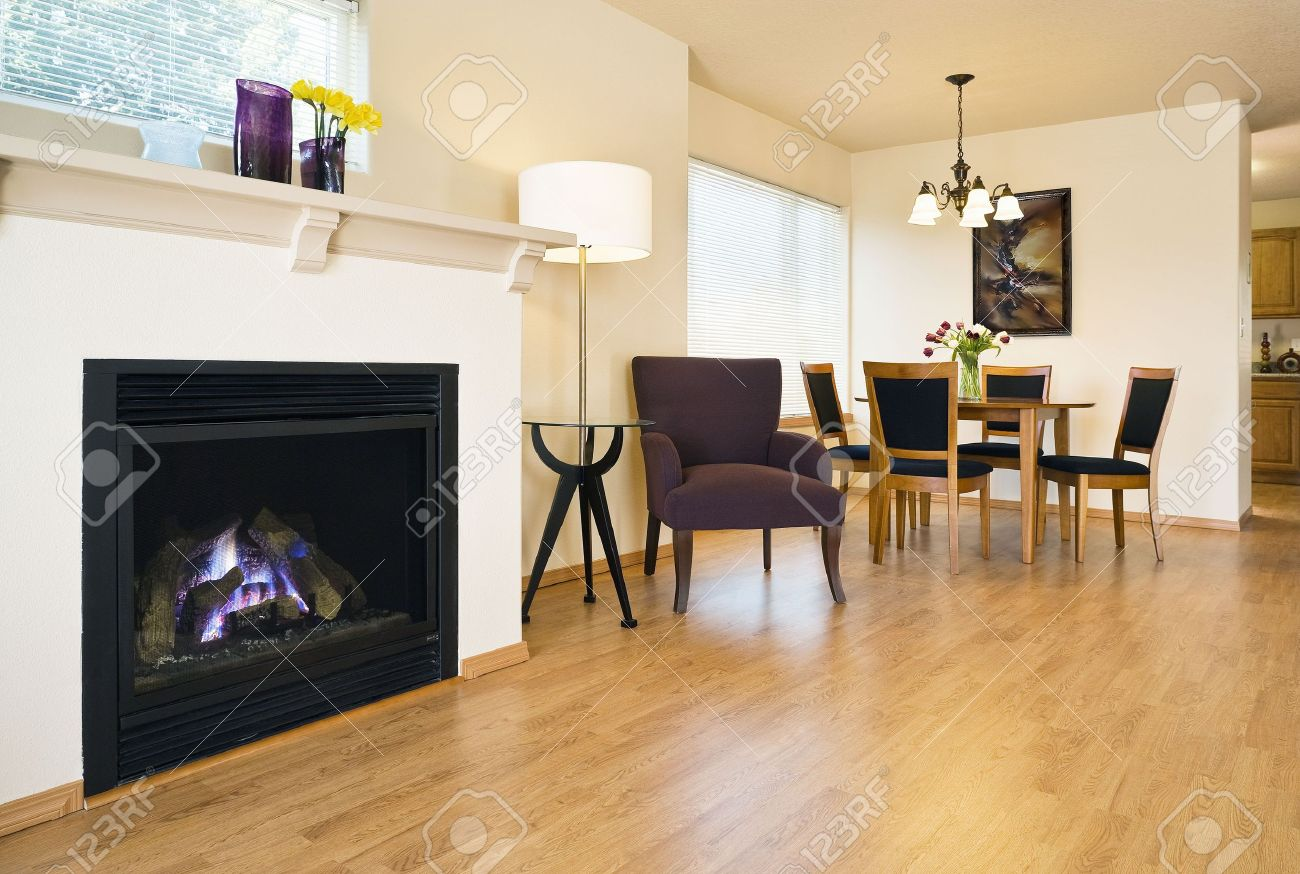 Spacious Living Area With Hardwood Floors A Fireplace And Dining Table Are In View