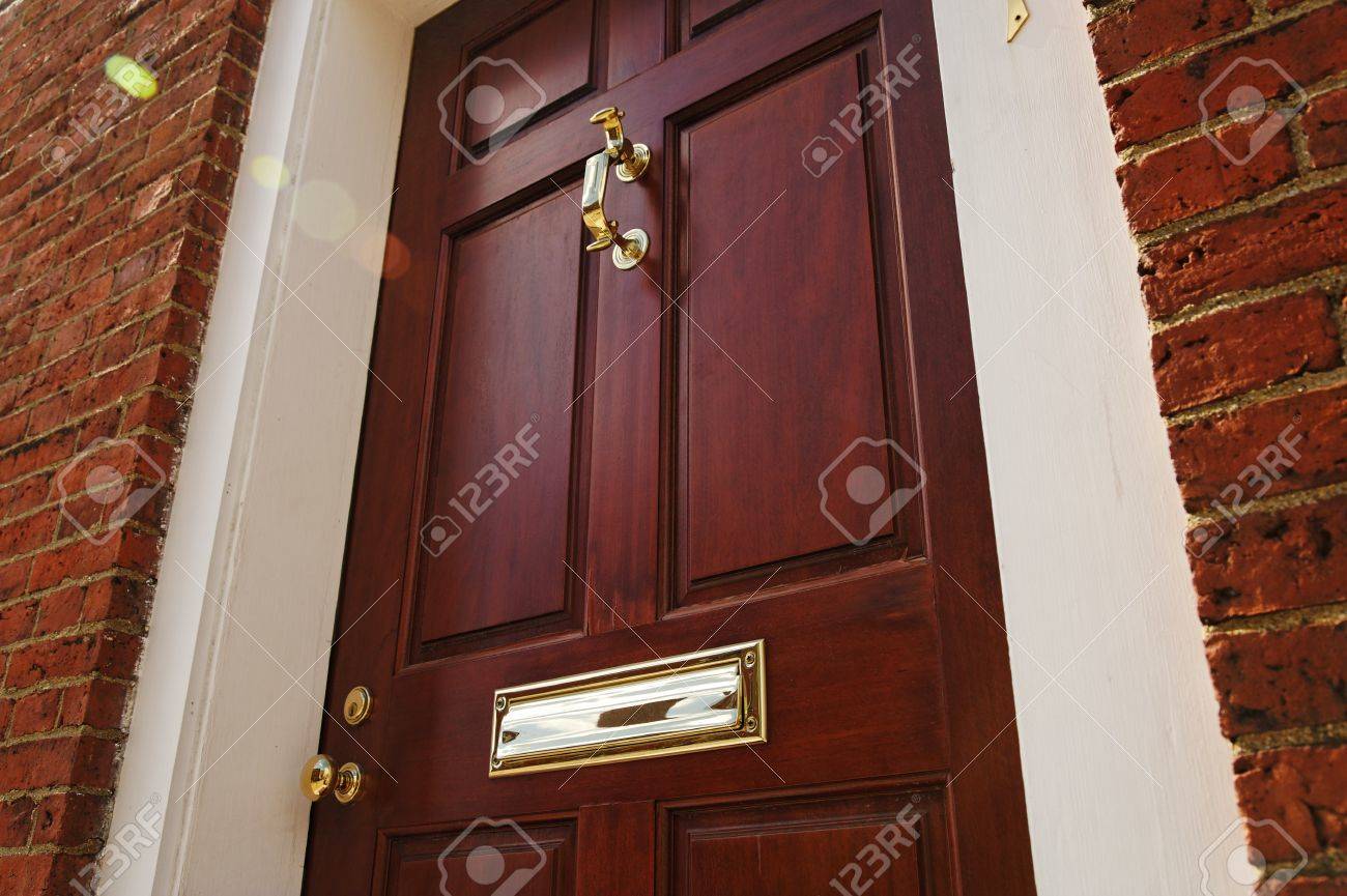Low Angle View Of An Elegant Red Door With Brass Accents In A