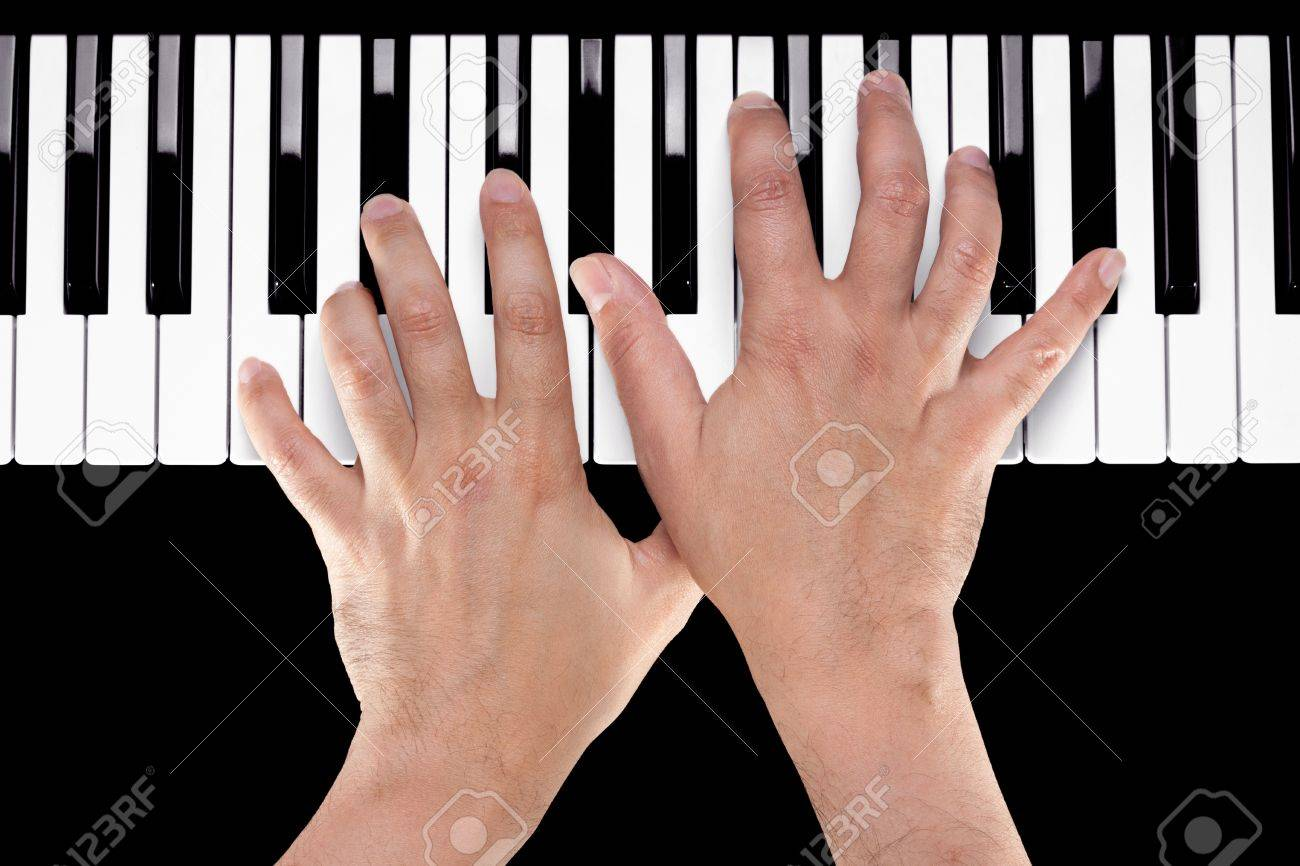 Hands playing a chord of Ab major over C bass on a piano keyboard shot from above with a black background. Stock Photo - 17718596