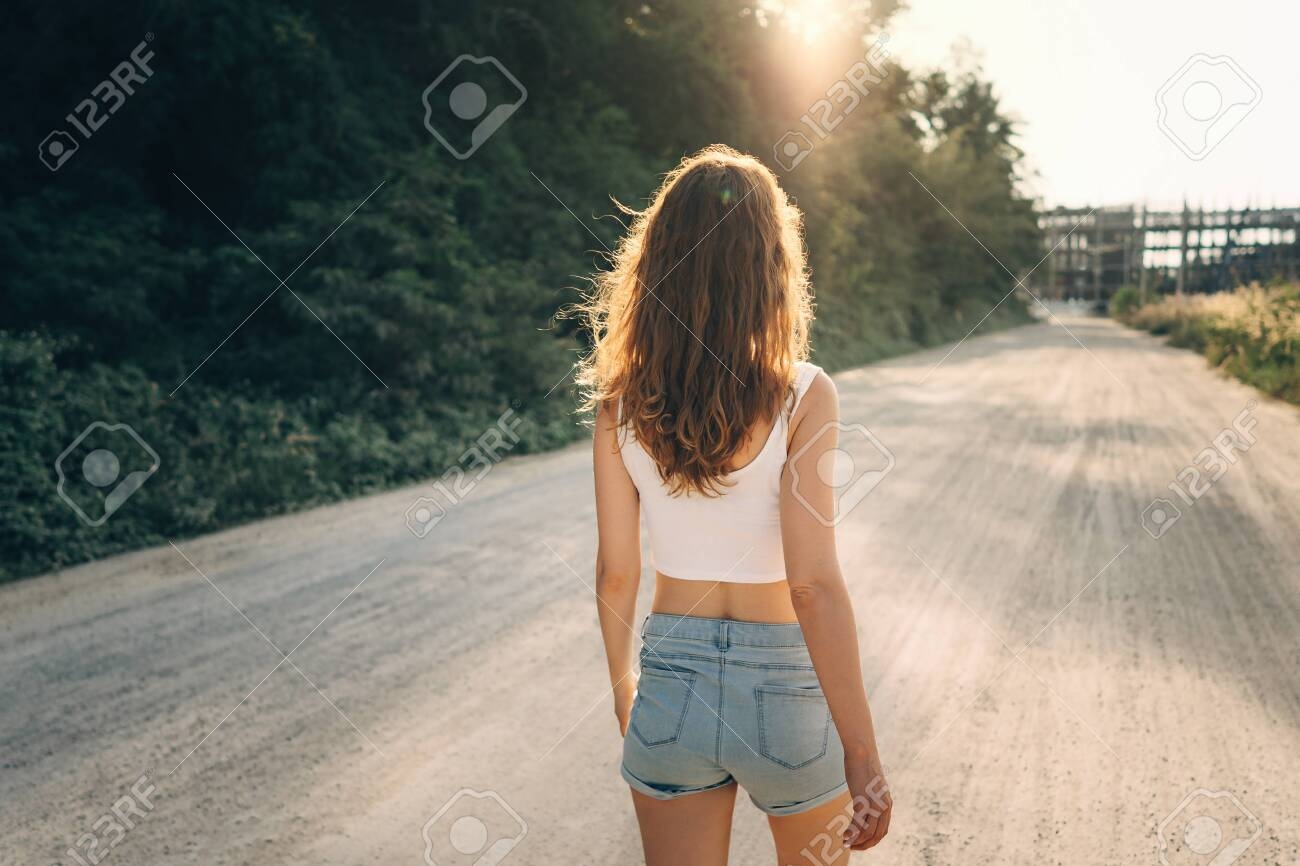 A young slender woman with loose hair walks in the summer on the road ahead in direct sunlight. Rear view - 126184817