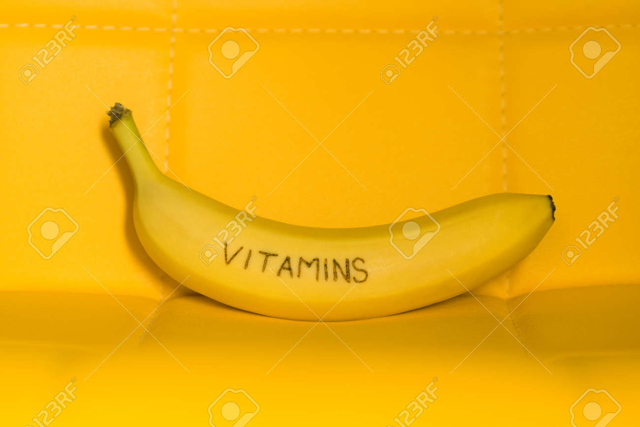 One fresh ripe banana fruit with text vitamins on yellow background - 170079623